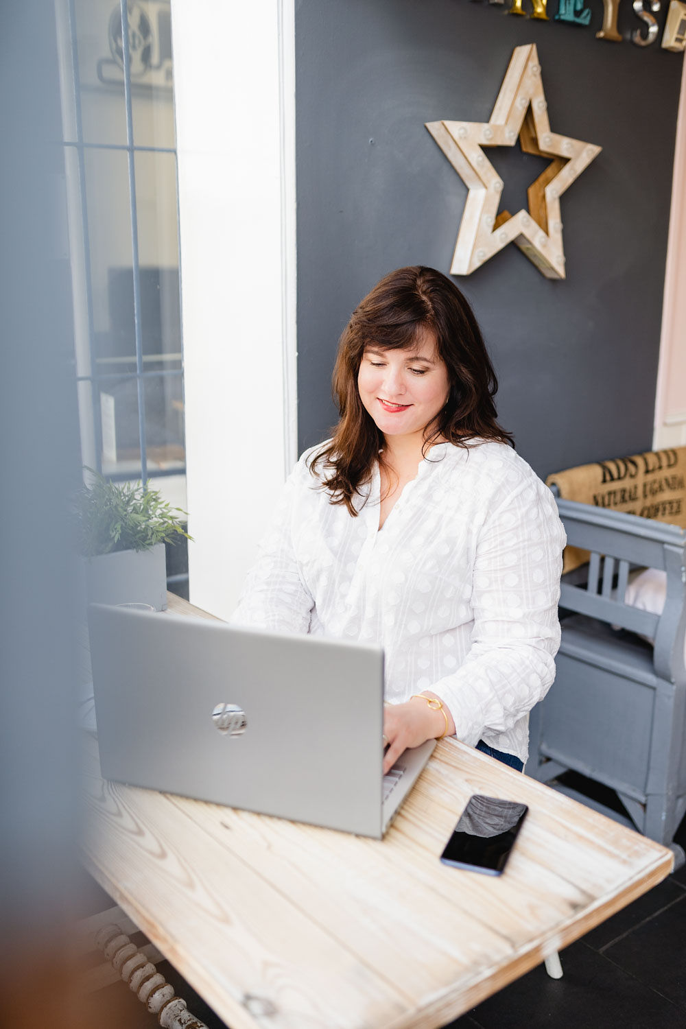 I'm sitting at a window table in a café. There's a white, wooden star on the wall (dark grey) behind me. On the table, you can see my open laptop and phone. I have long dark hair and am wearing a long-sleeved white shirt; I'm looking at the laptop and typing.