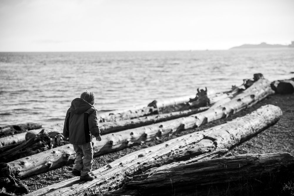 boy with epilepsy walks on driftwood
