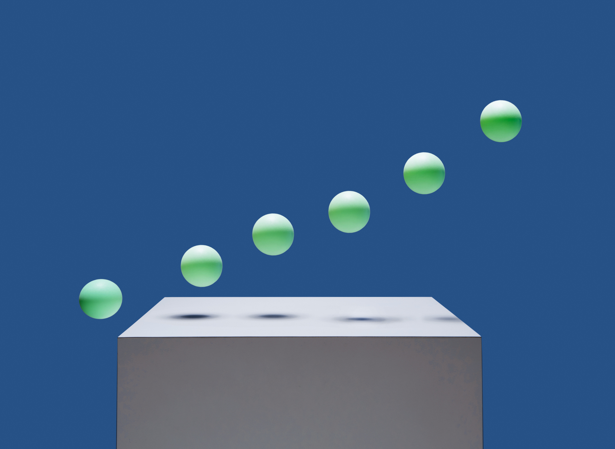 6 green balls bouncing off of white box in ascending order, blue background