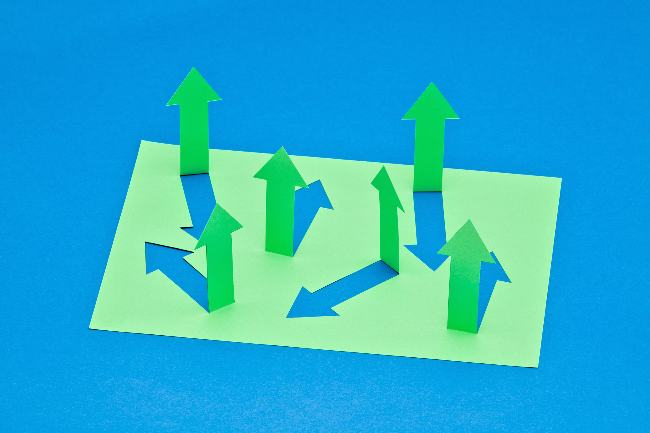 Green arrows cut out from a sheet of paper