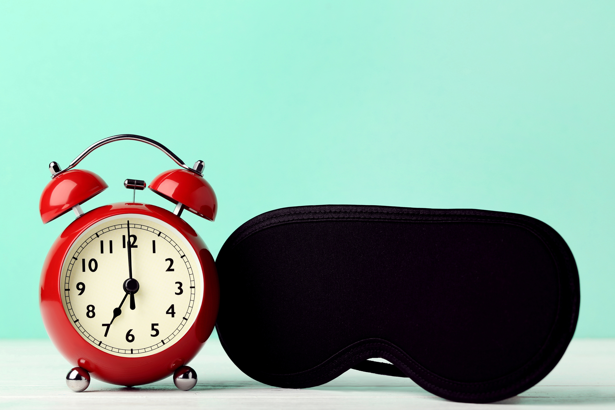 Red alarm clock with sleeping mask on mint background