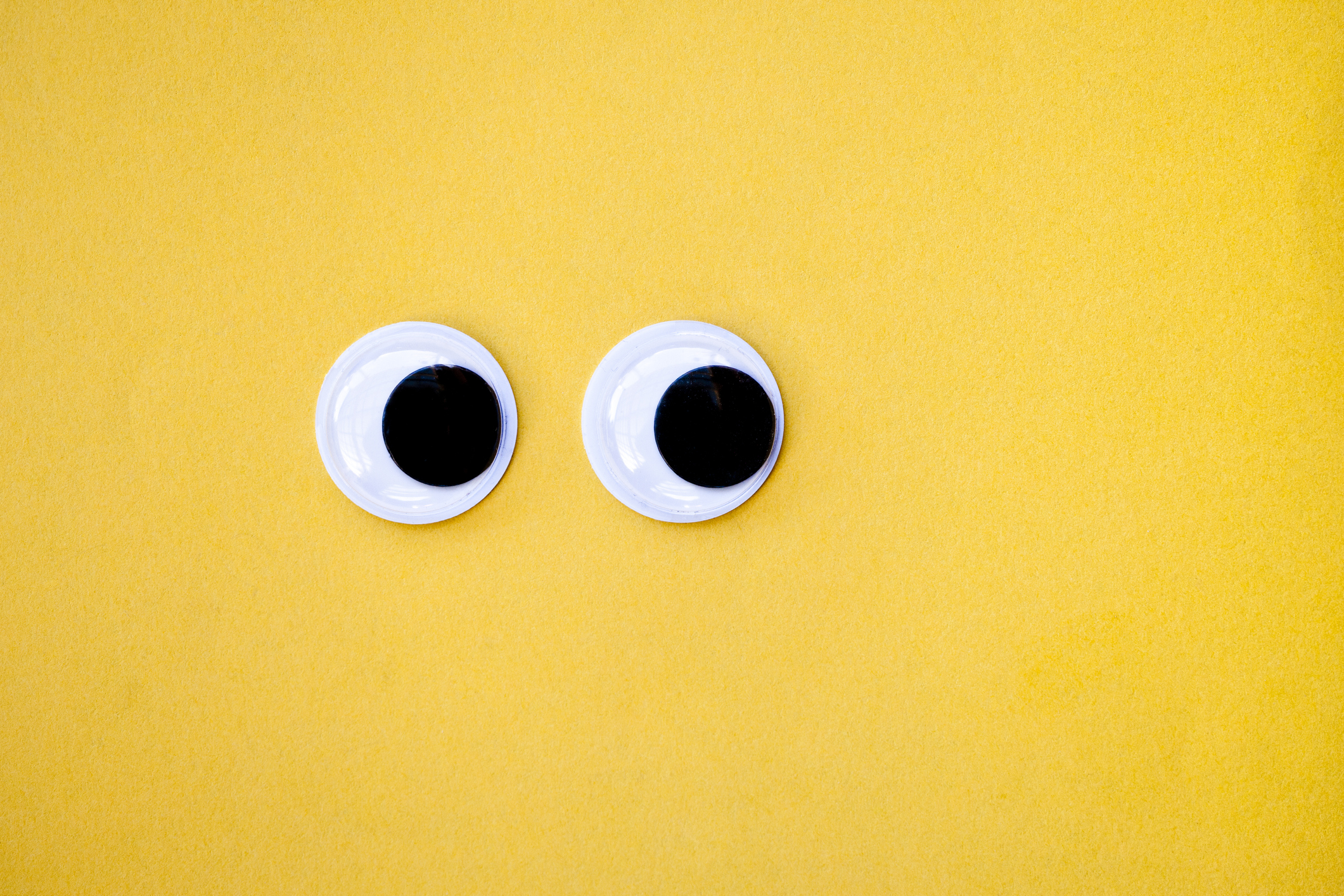 Googly eyes on a yellow background, looking sideways.