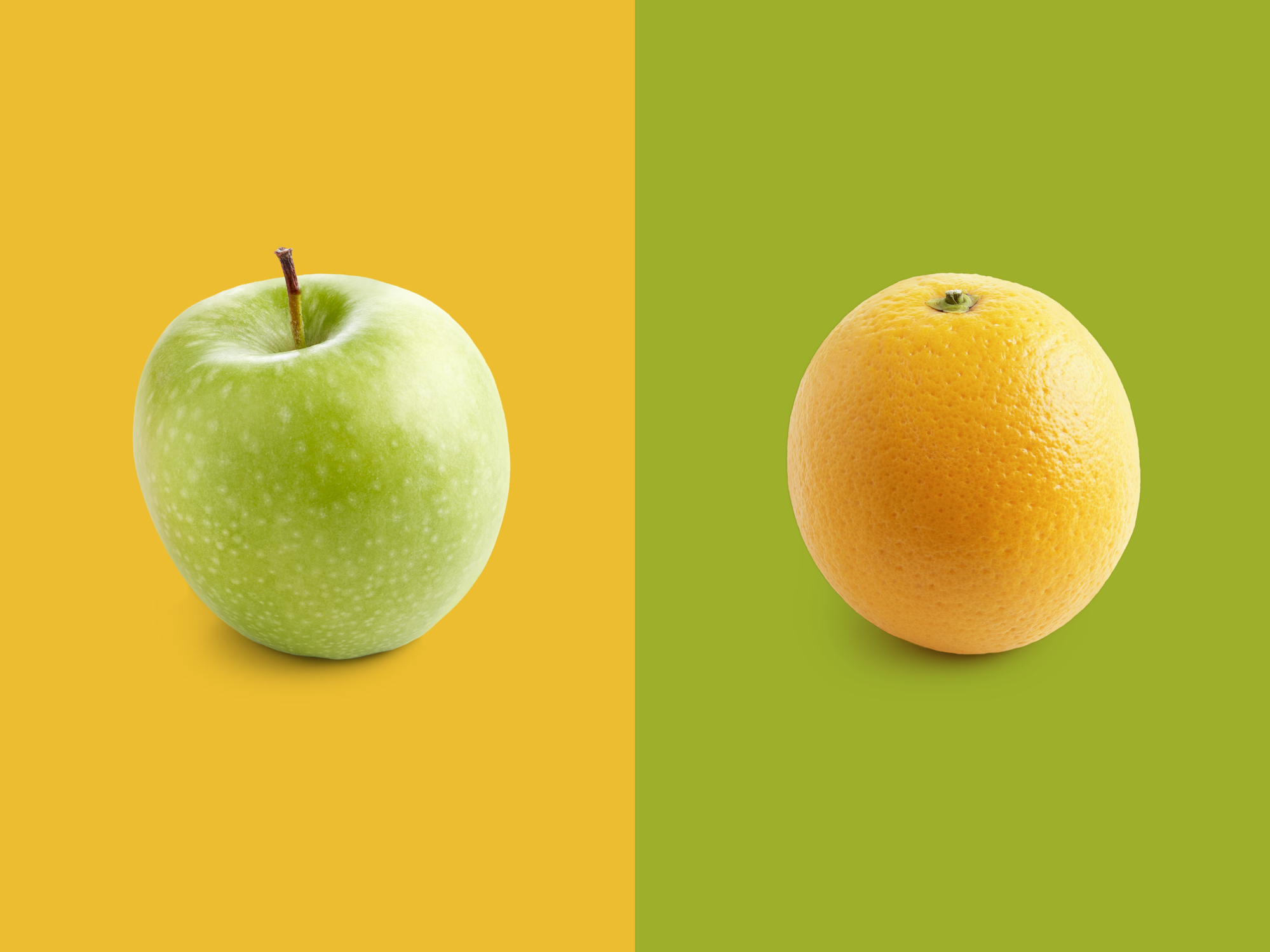 Apple and orange against yellow and green background.