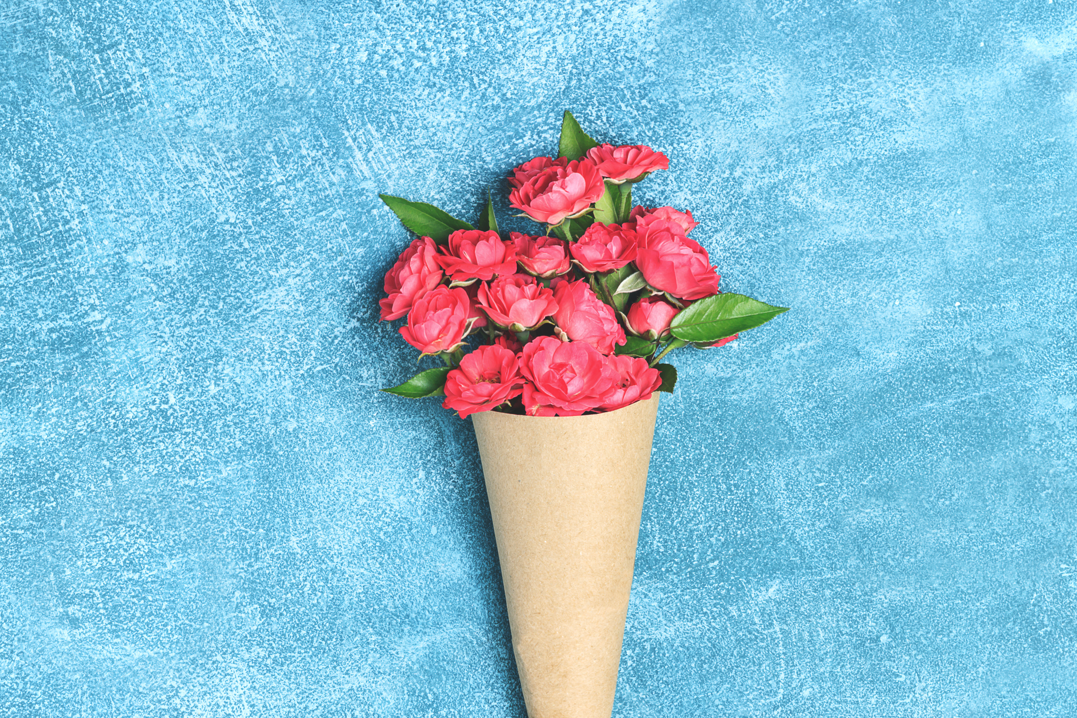 Beautiful bouquet of small red roses in vintage paper on the table. Top view, flat lay, overhead. Invitation card. mothers day background. Floral invite card