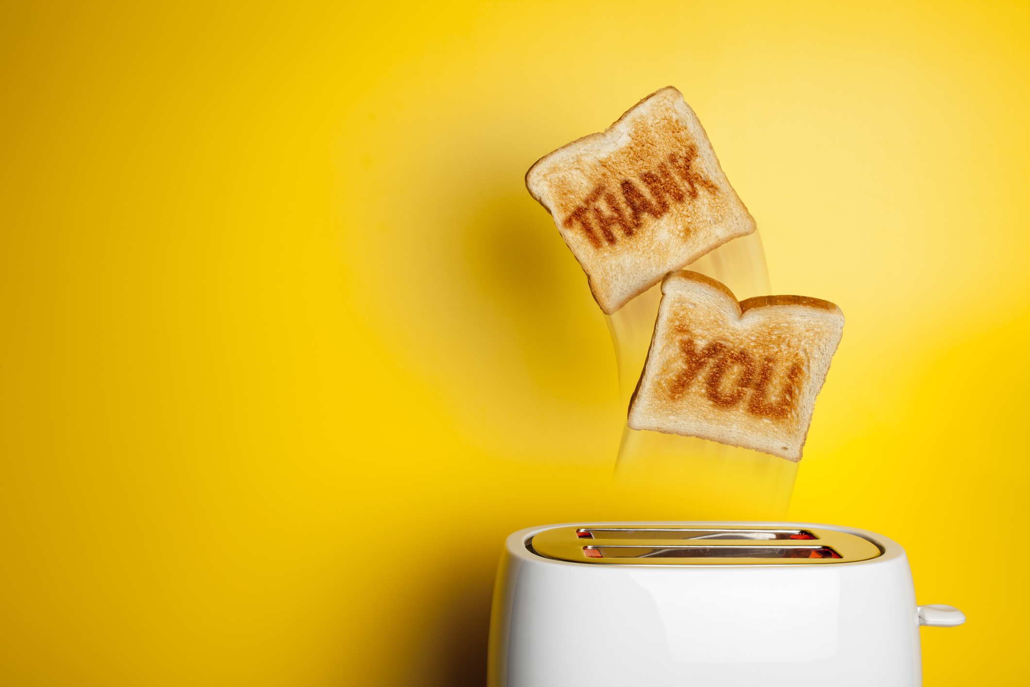 Concept photograph of fresh toast bread jumping out of the toaster.
