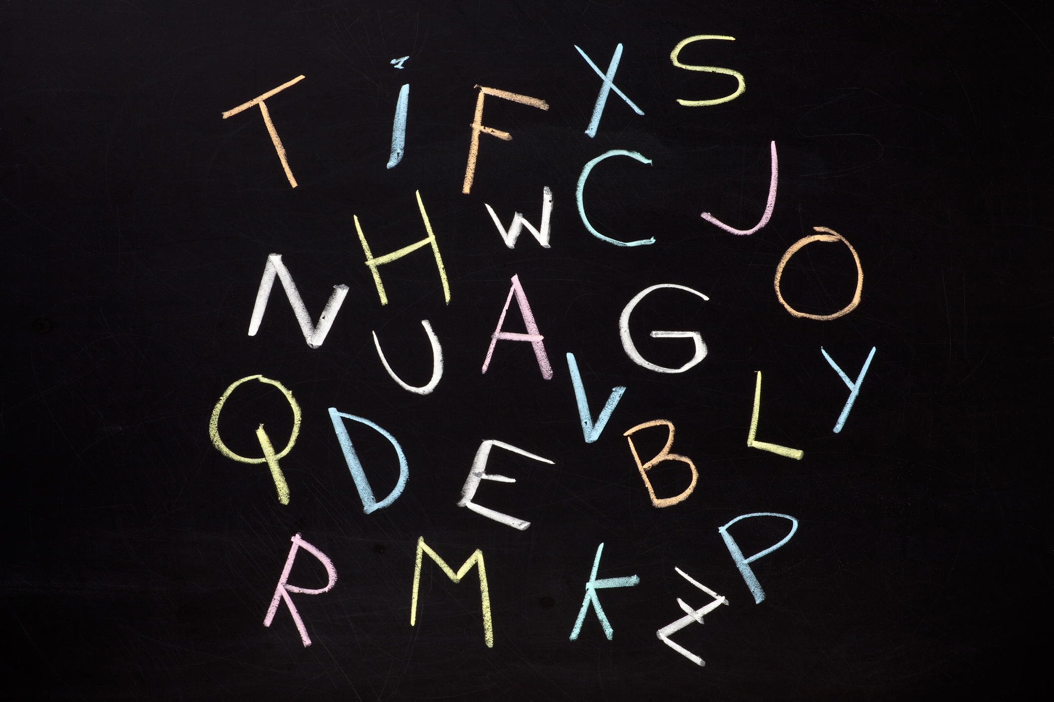The letters of the alphabet drawn in blackboard without any particular order