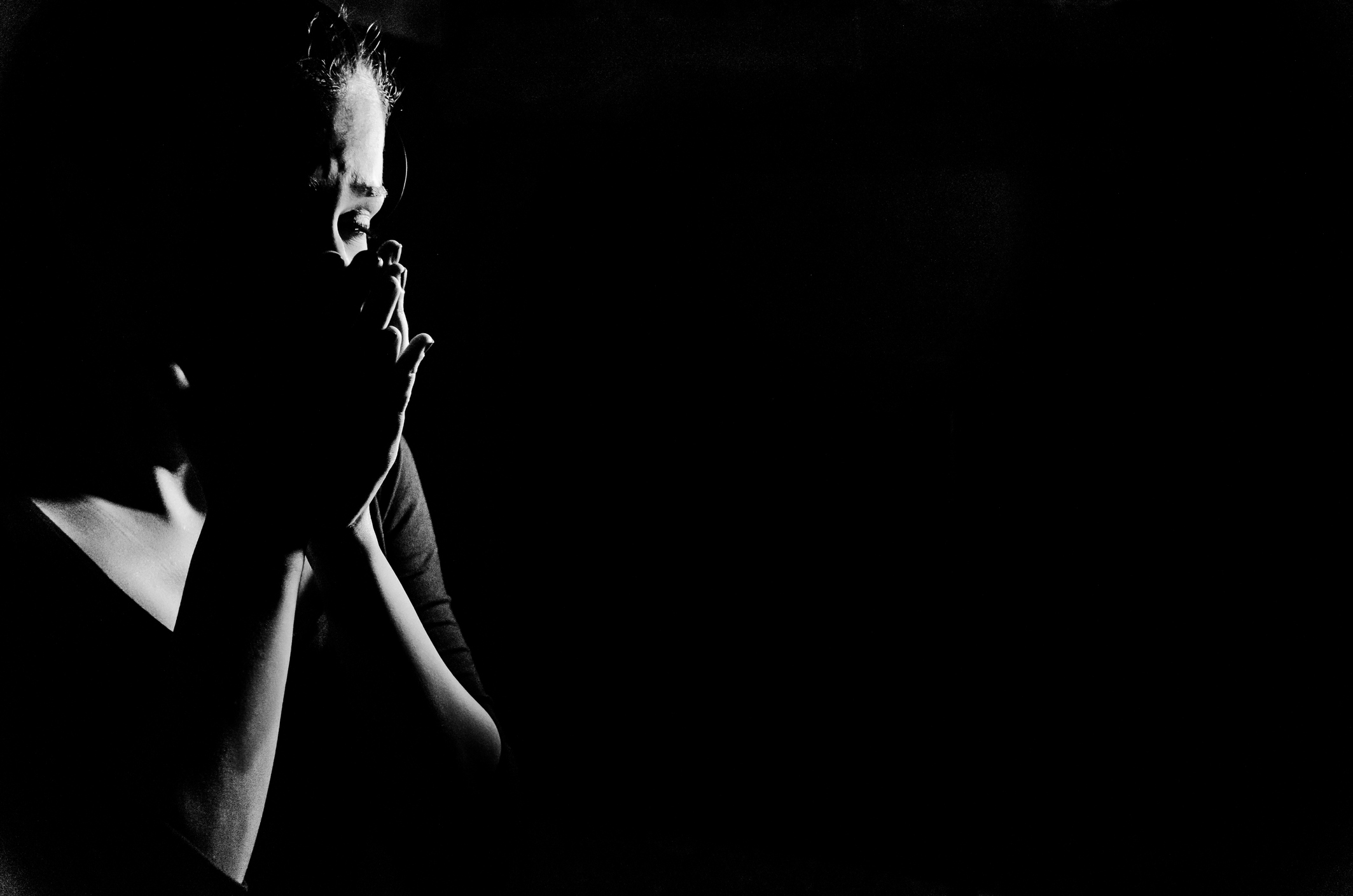 Young woman stanging in the dark crying,she is feeling hopless .