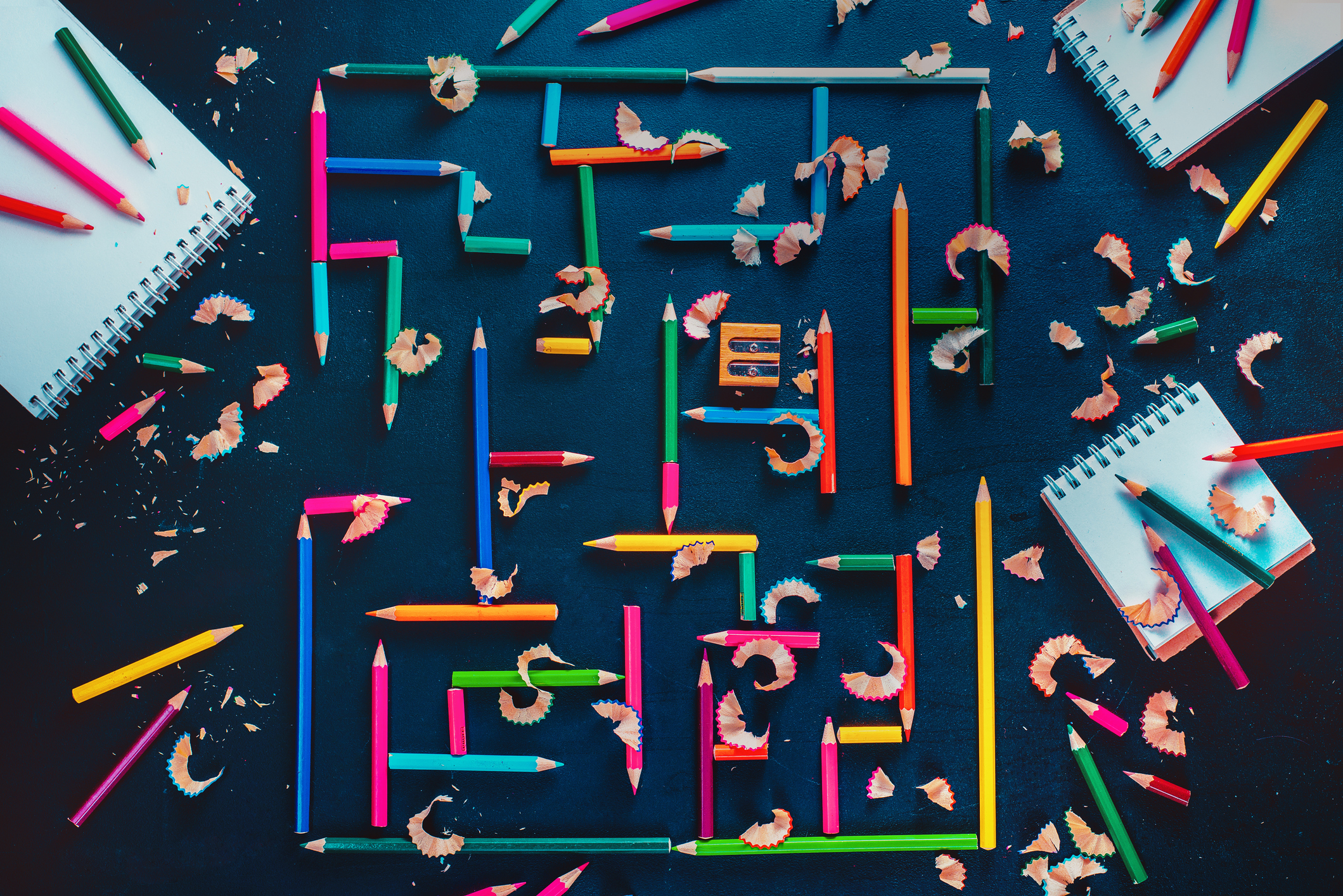 Conceptual still life with notepads, paper, and a labyrinth made of coloured pencils on a dark wooden background