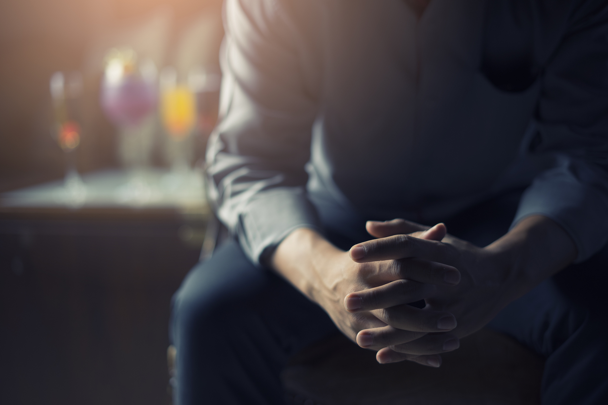 very Tired or stressed businessman hand touching head and sitting in front of cocktail and alcohol drink with darken mood and tone filter business concept and health concept