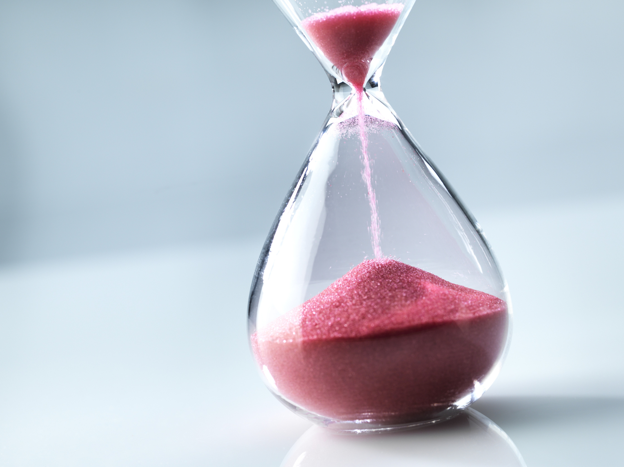 Sand flowing through an hourglass.