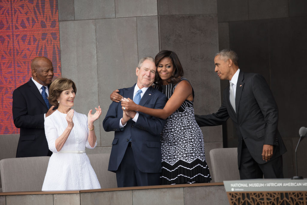 First Lady Michelle Obama hugs former President George W Bush at the opening of the National Museum of African American History and Culture, Washington DC, September 24, 2016. On stage with them are Congressman John Lewis, former First Lady Laura Bush, and President Barack Obama. (Photo by David Hume Kennerly via Bank of America/Getty Images)