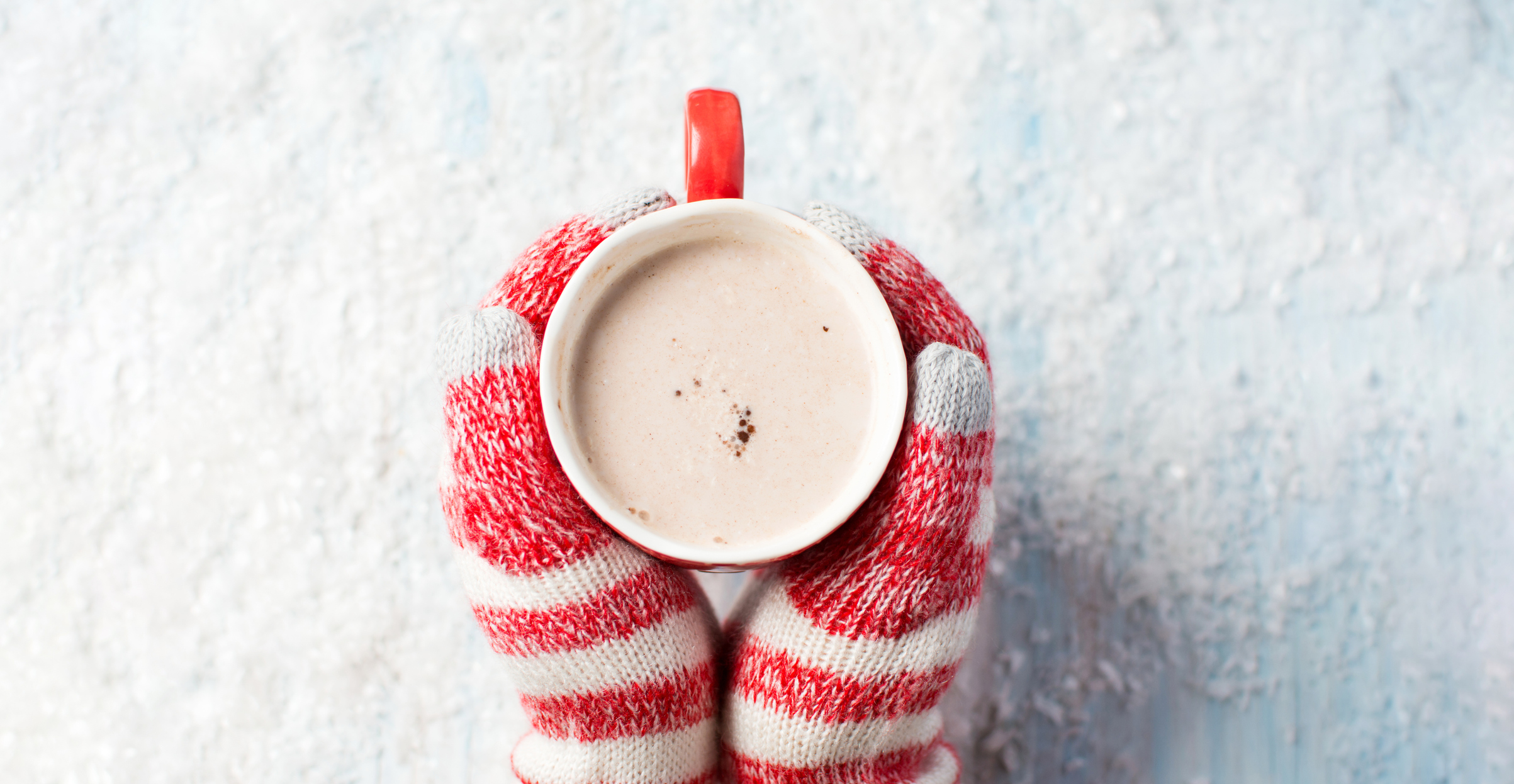female hands in gloves holding hot chocolate over a snowy background