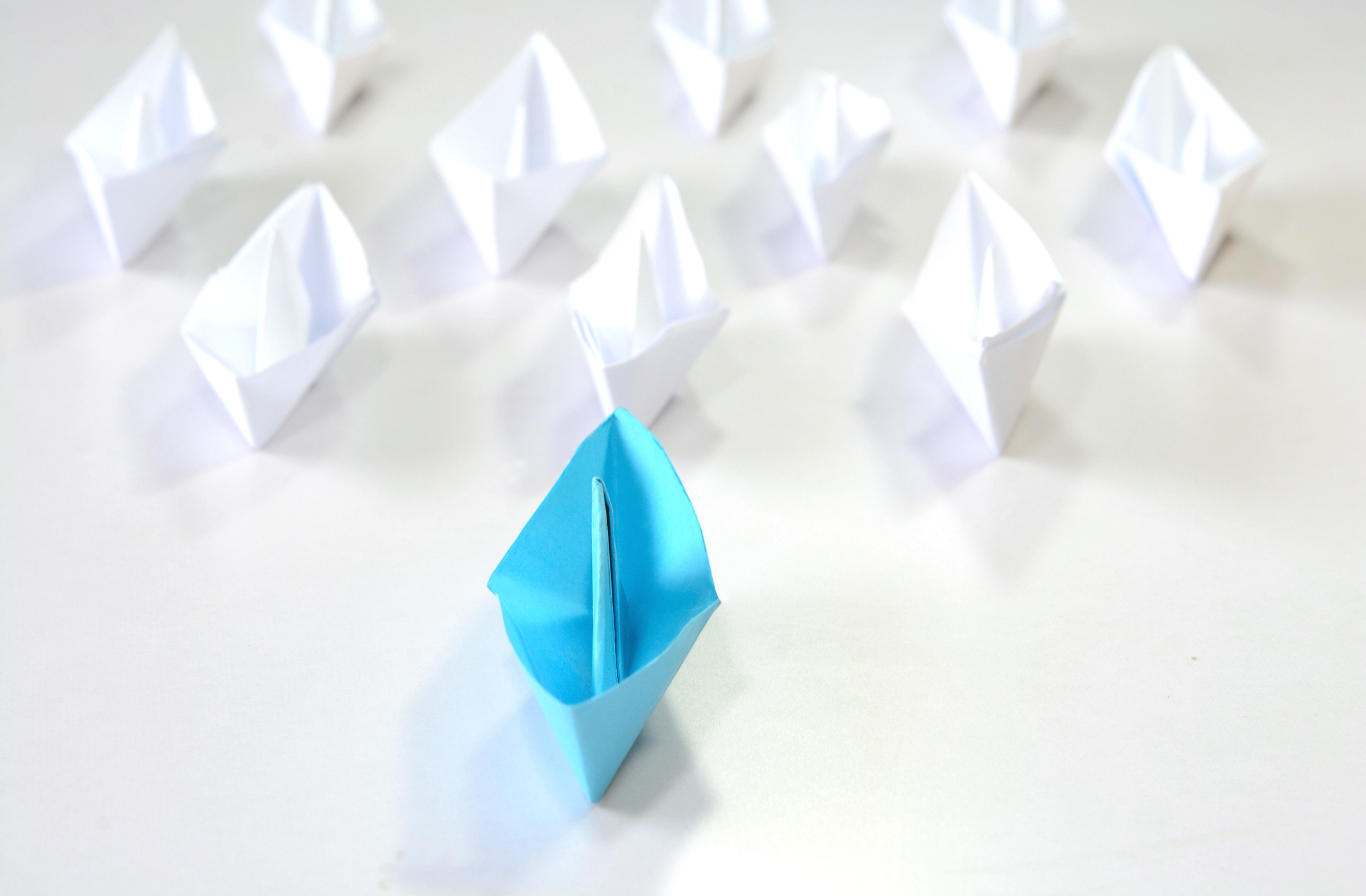 Leading from the front. Leadership concept of blue origami ship leading in the front.