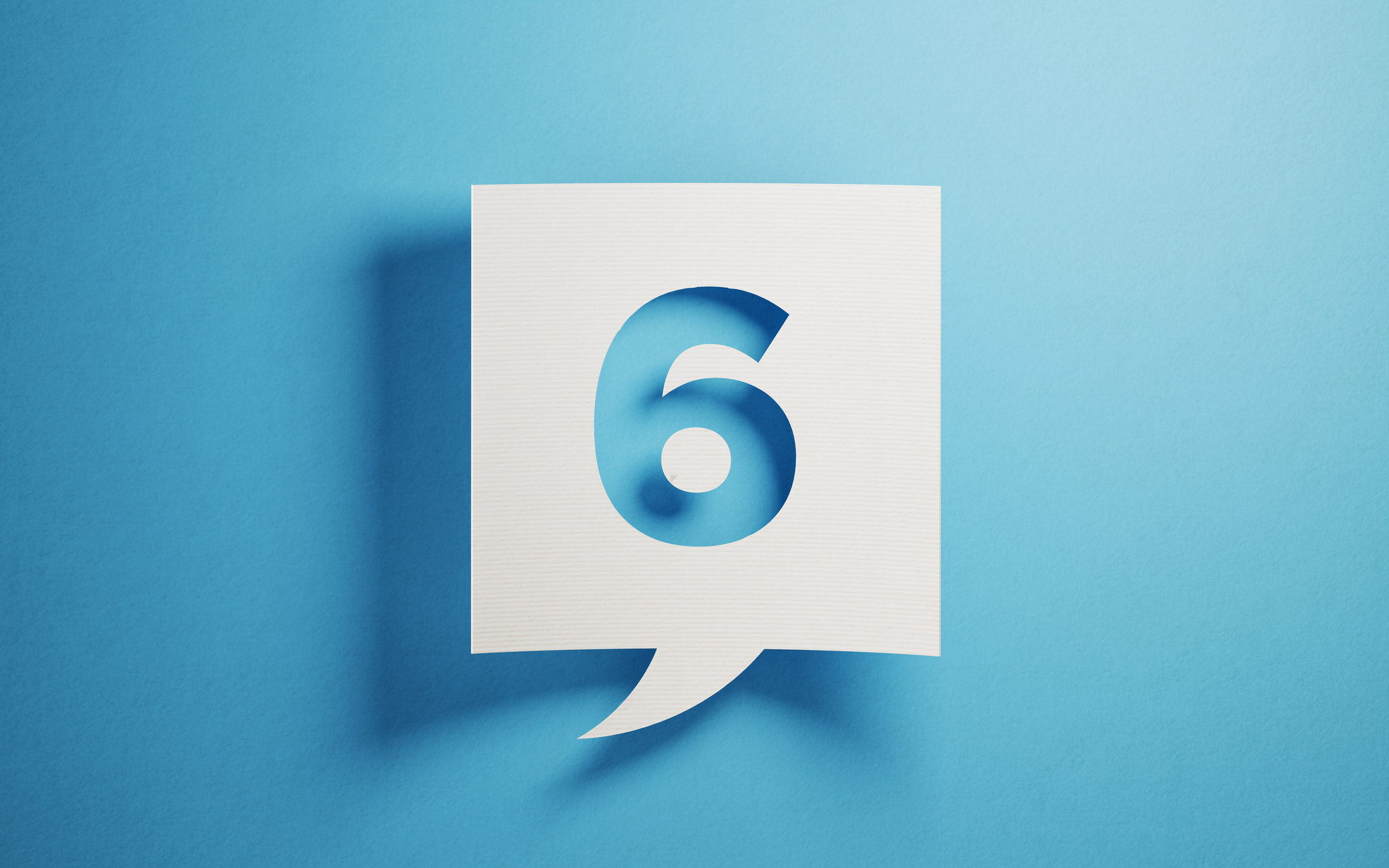White chat bubble on  blue background. Number six writes on chat bubble. Horizontal composition with copy space.
