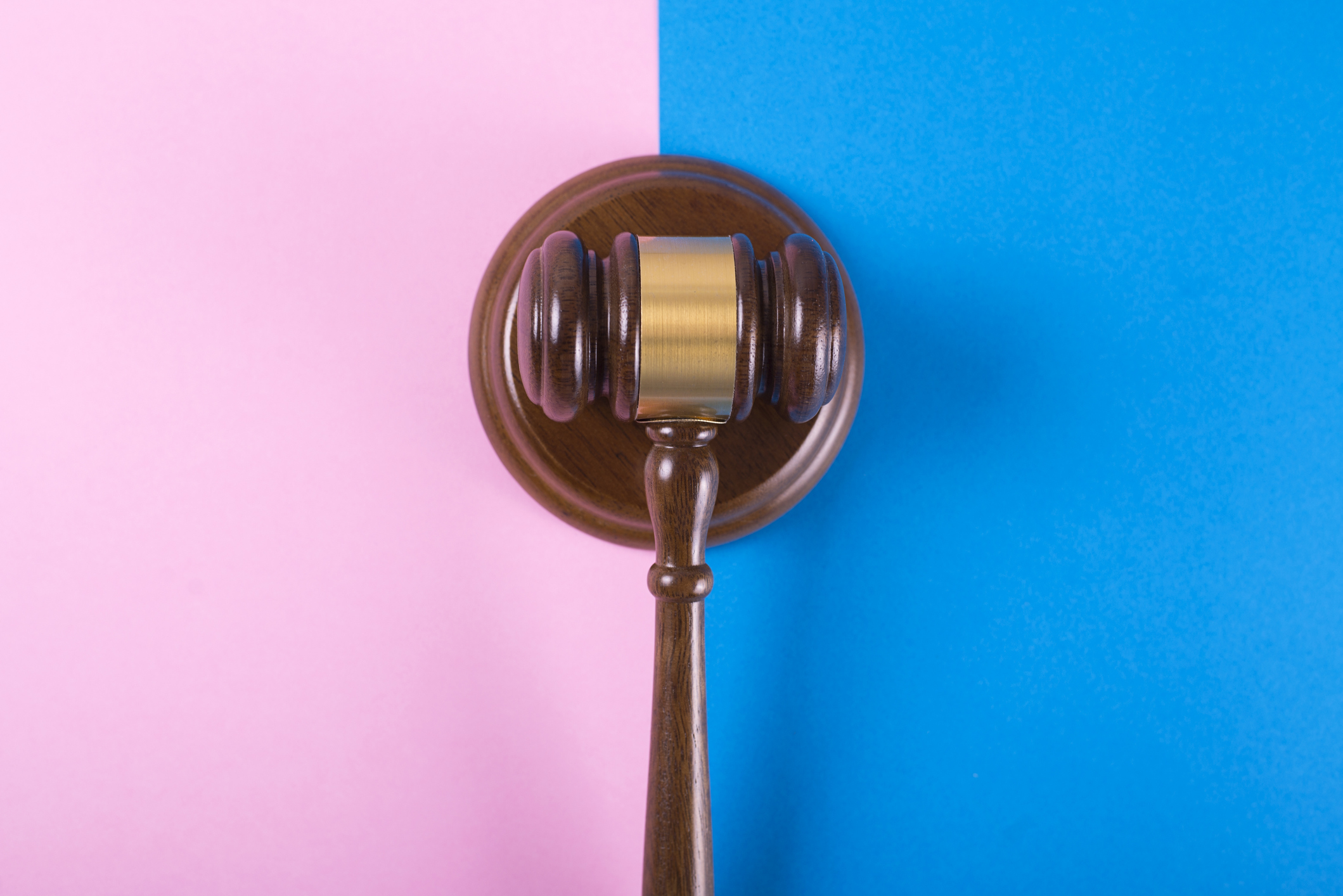 Judge gavel or auction on pink and blue background. Justice and auction.