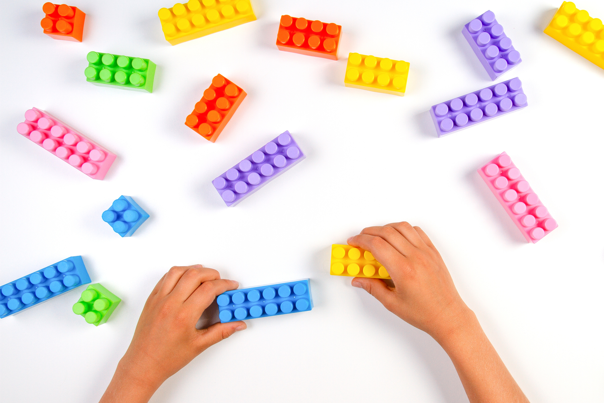 Kid hands play with colorful plastic construction blocks on white background. Top view