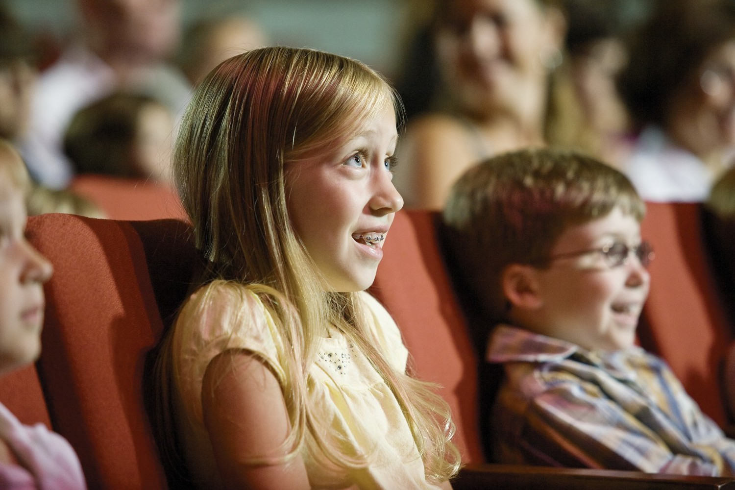Sister and brother sitting in theatre seats