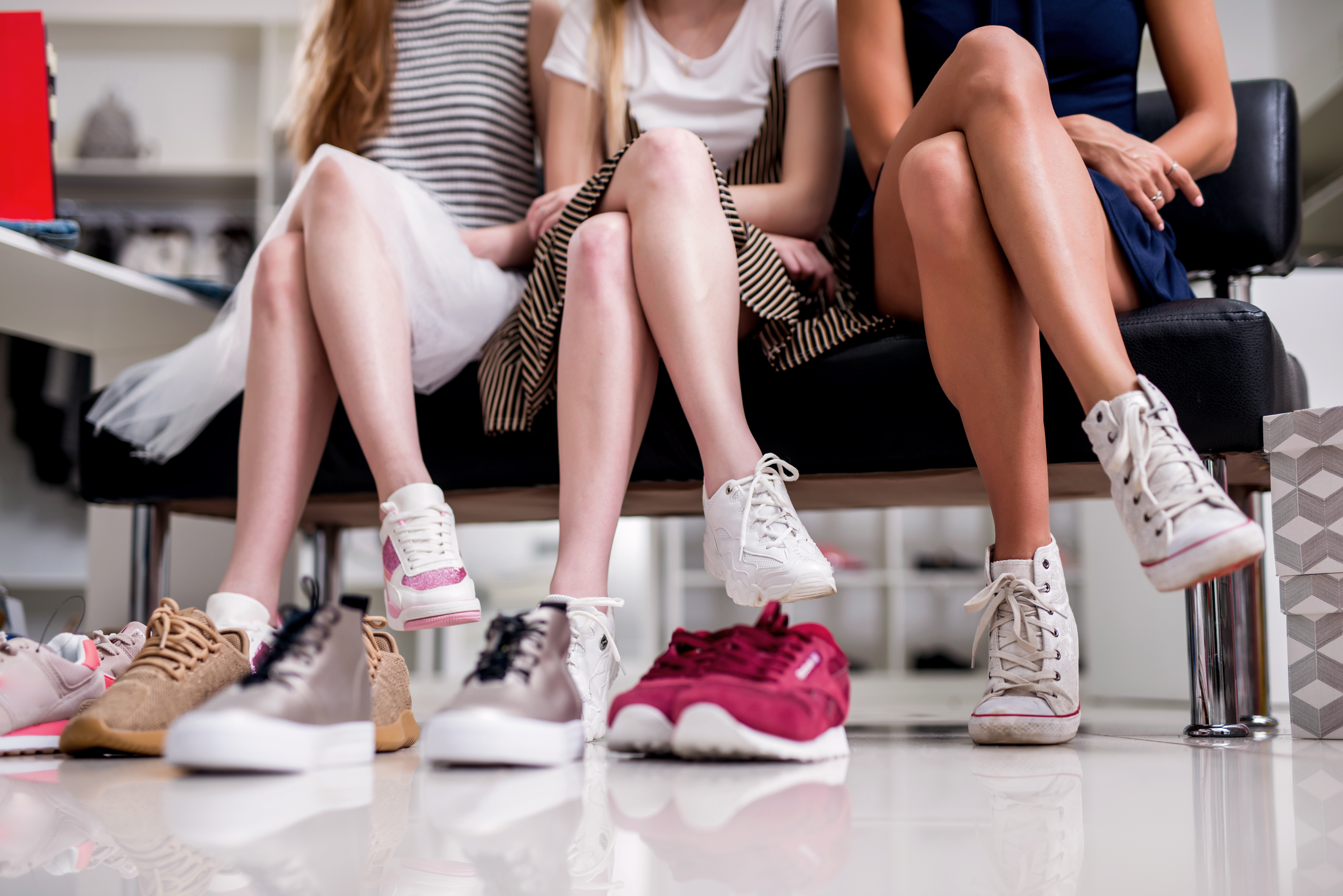 Close-up image of women sitting with legs crossed trying on new sneakers in shopping center.