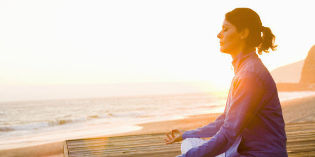 Woman meditating on deck at  beach, side view
