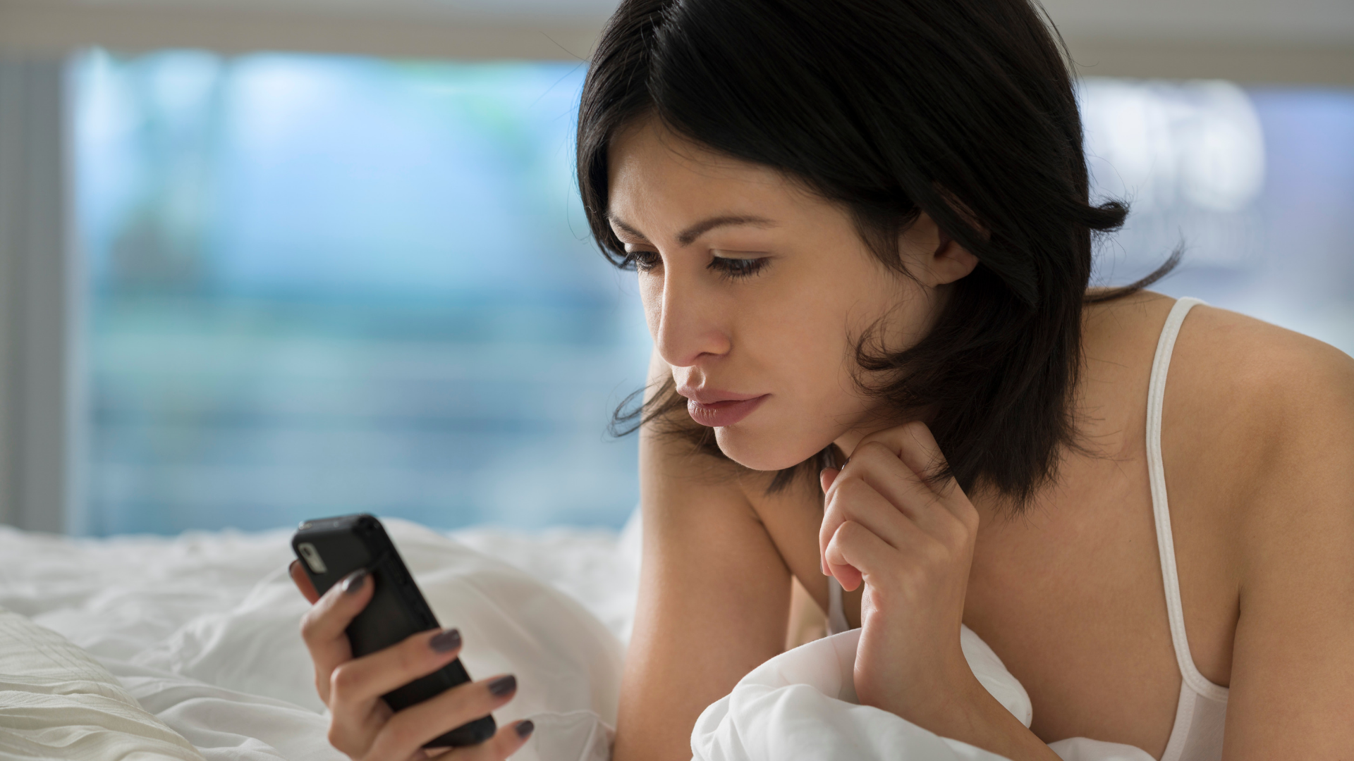 woman checking her phone in the morning