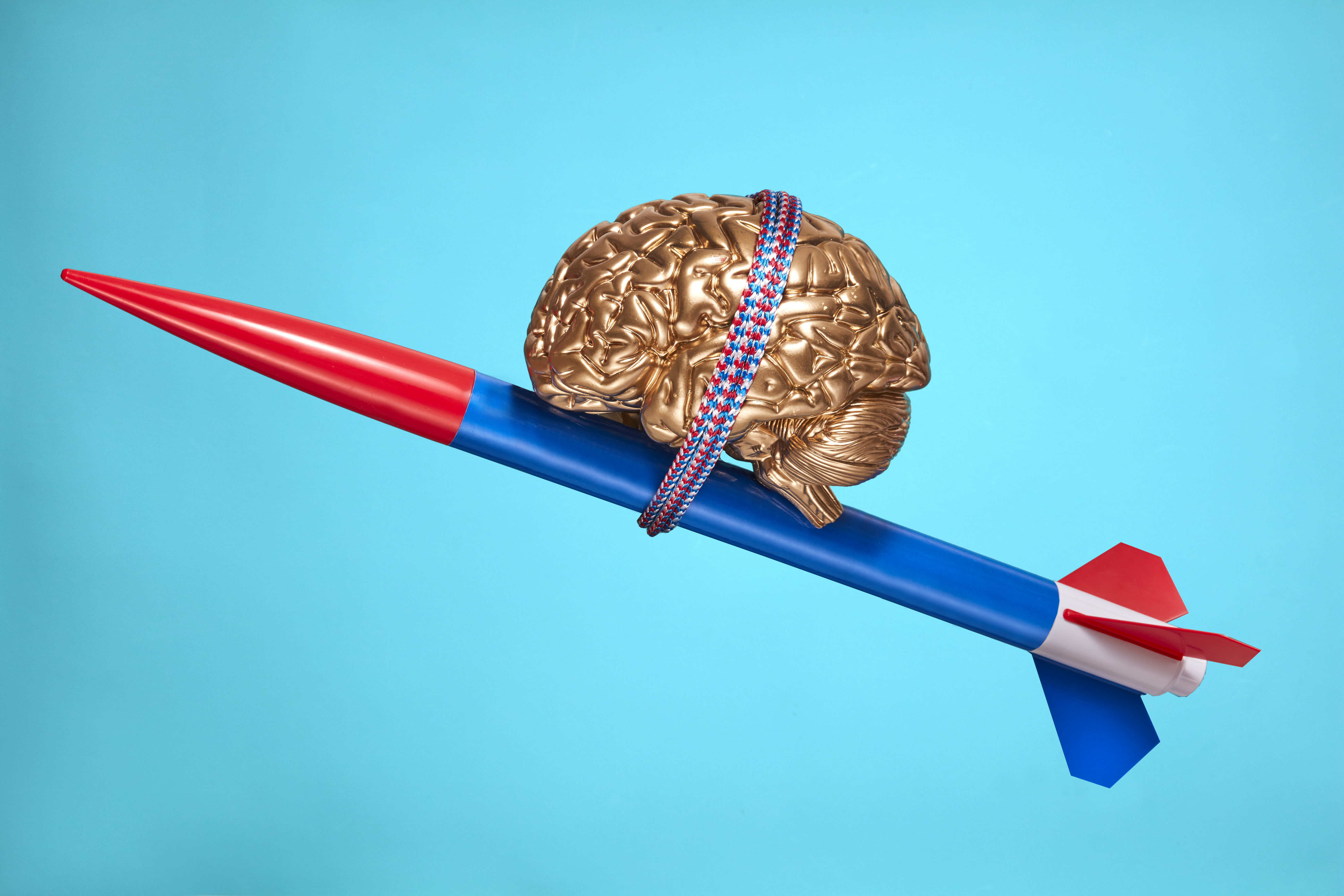 A model brain atop a rocket symbolizes innovation, progress, and psychology topics.