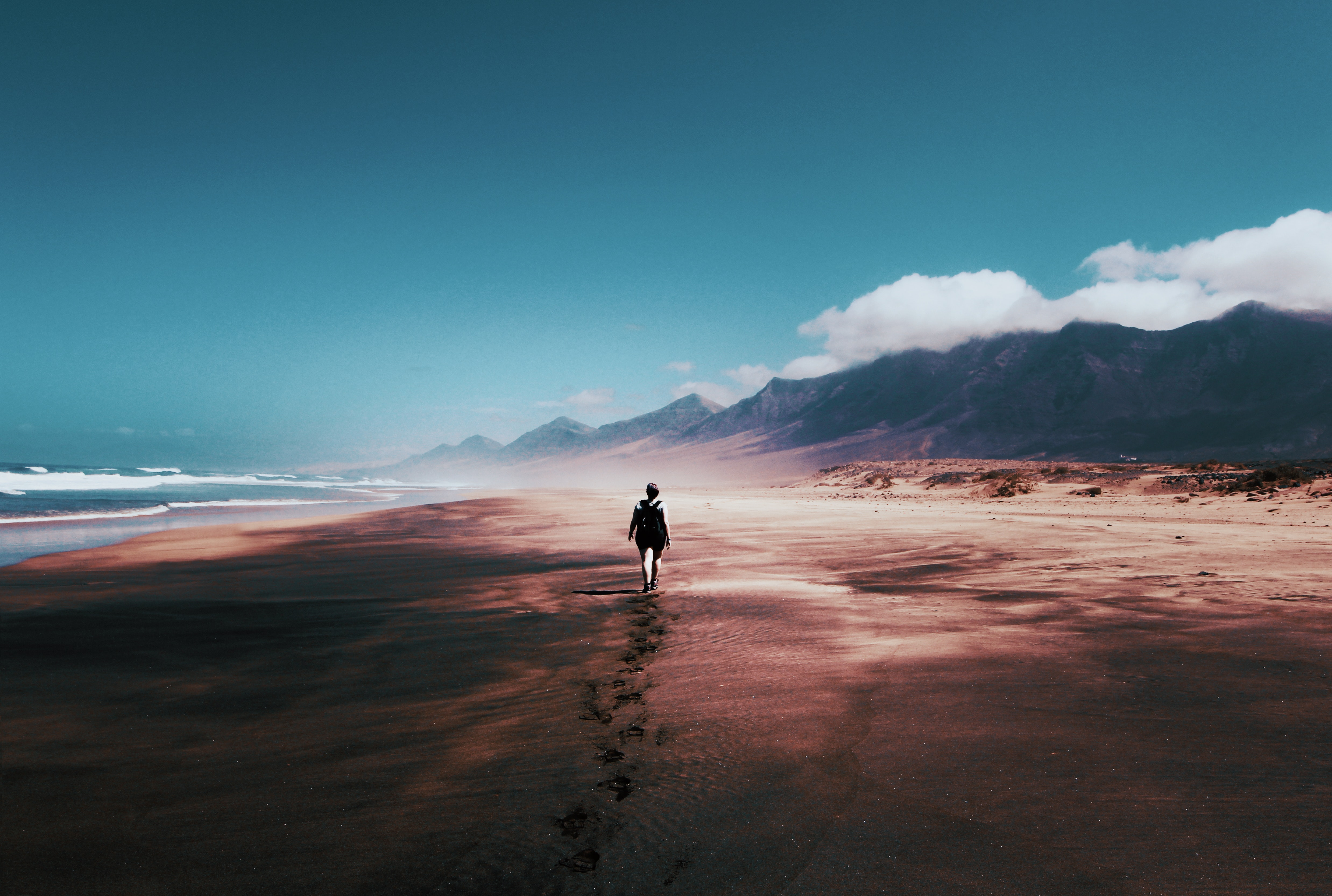 A person walks on a wide beach expanse
