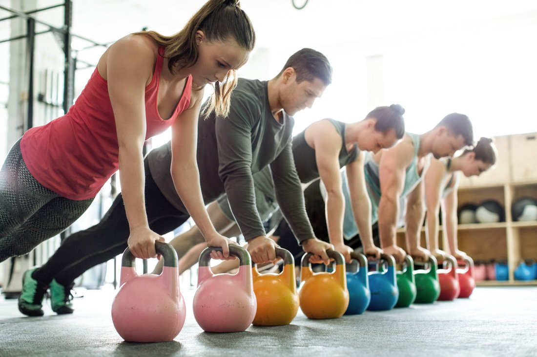 Group of young men and women doing push-ups on kettlebells in a gym