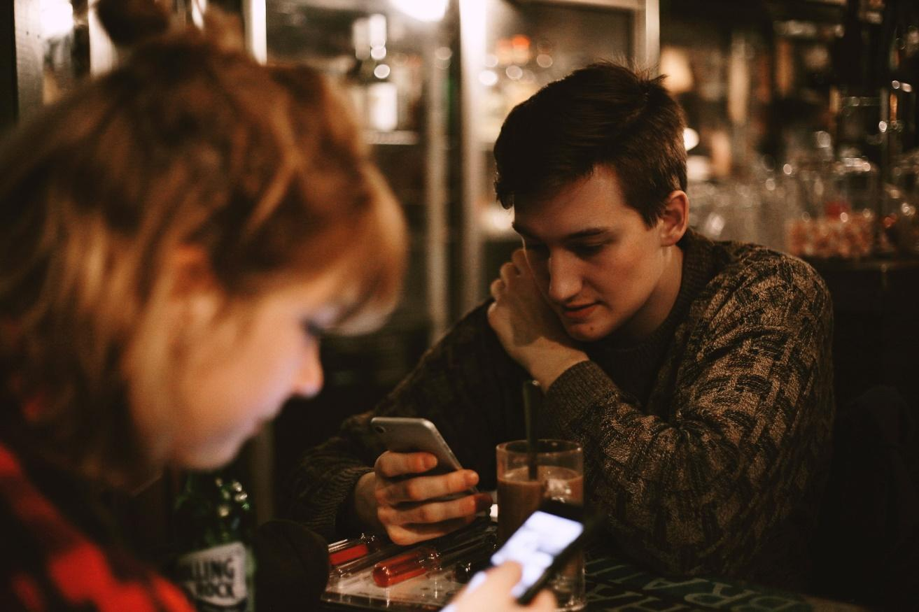 a couple on their phones looking at dating apps