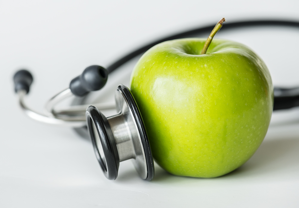 Closeup of an apple and a stethoscope healthy food and health concept