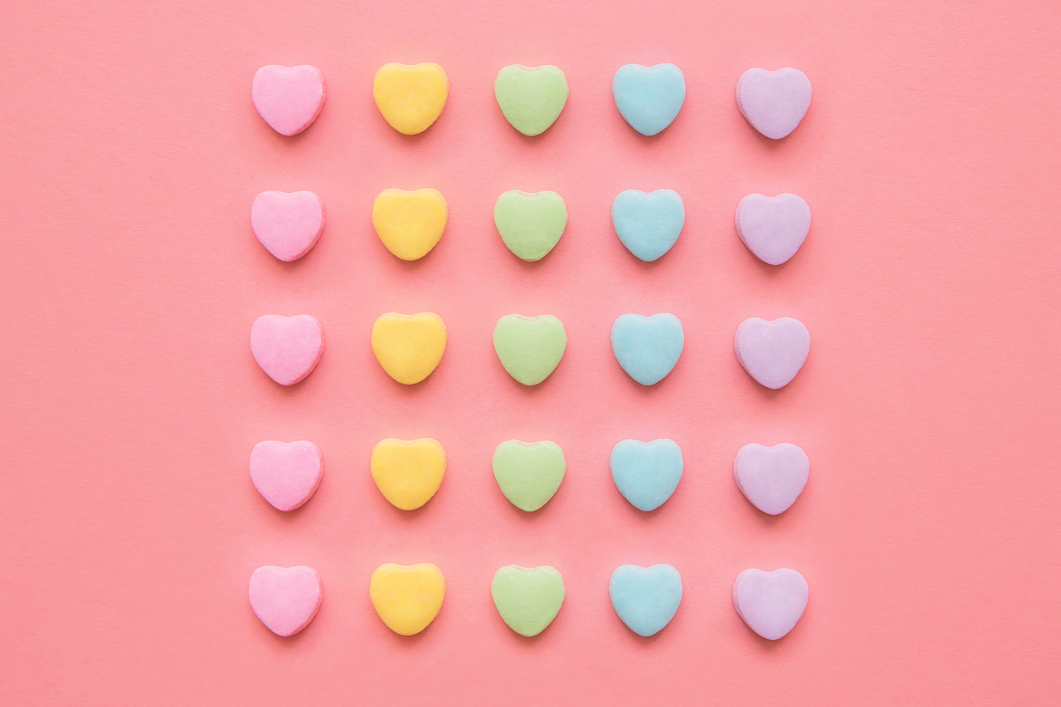 Love hearts background. Candy hearts on a pink background for Valentine's Day or anytime. Conceptual image to symbolism dating, marriage and/or equality, gay pride, or OCD and order.