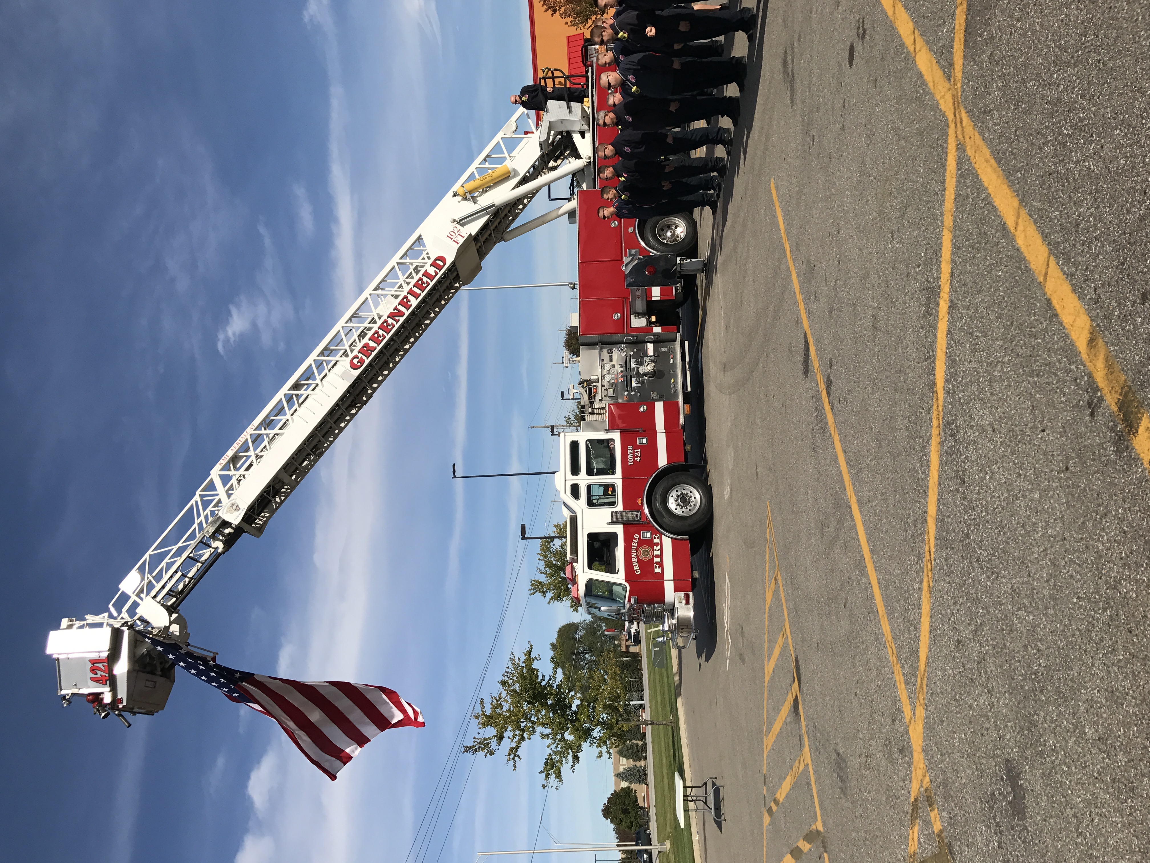 Red firetruck, the arm is lifted, and there's a flag hanging from the arm of the lift