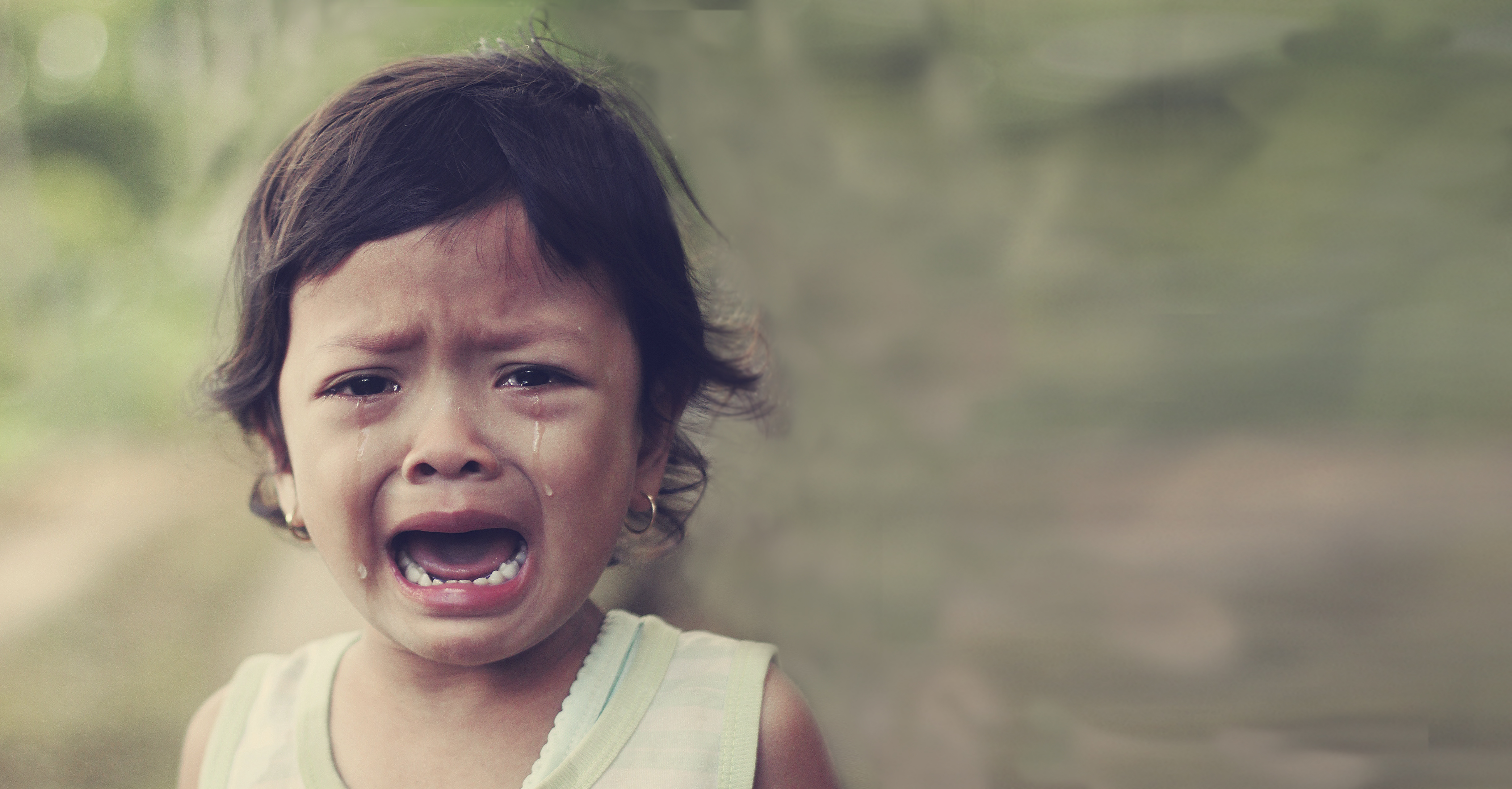 Young child crying in nature with tears streaming down her face