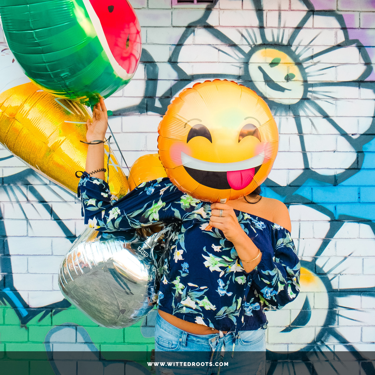 Woman in front of a wall mural, holding a smiley face emoji balloon in front of her face.