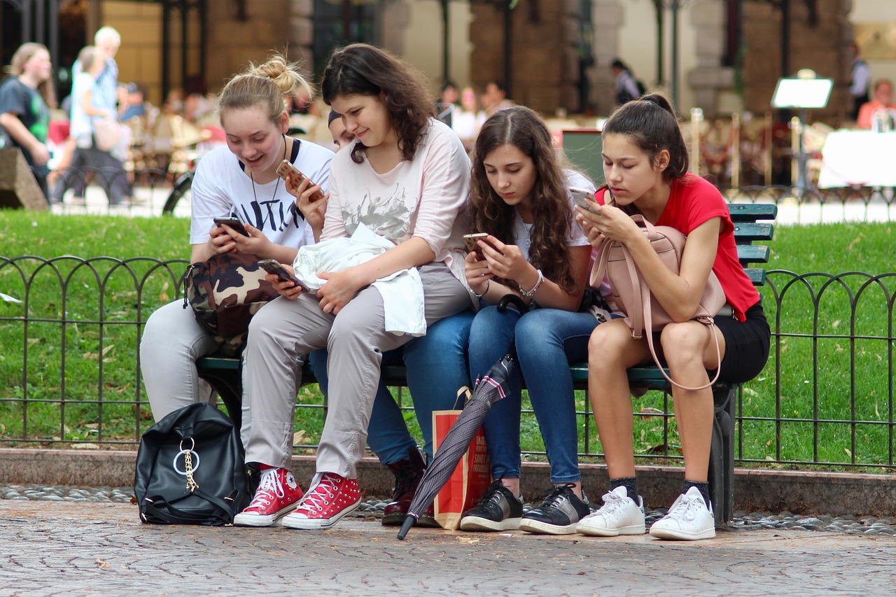 Closeup of teenage girls hands using cell phones outdoors