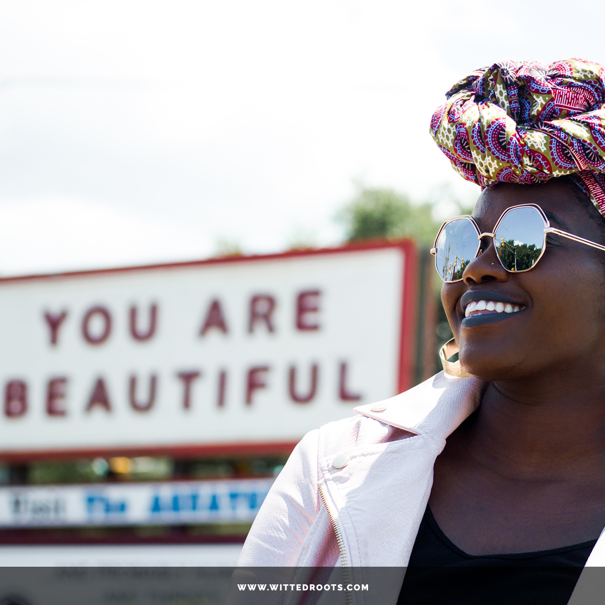 "Black woman wearing reflective sunglasses and headwrap, smiling off into the distance. The sign ""You Are Beautiful"" shows in the background."