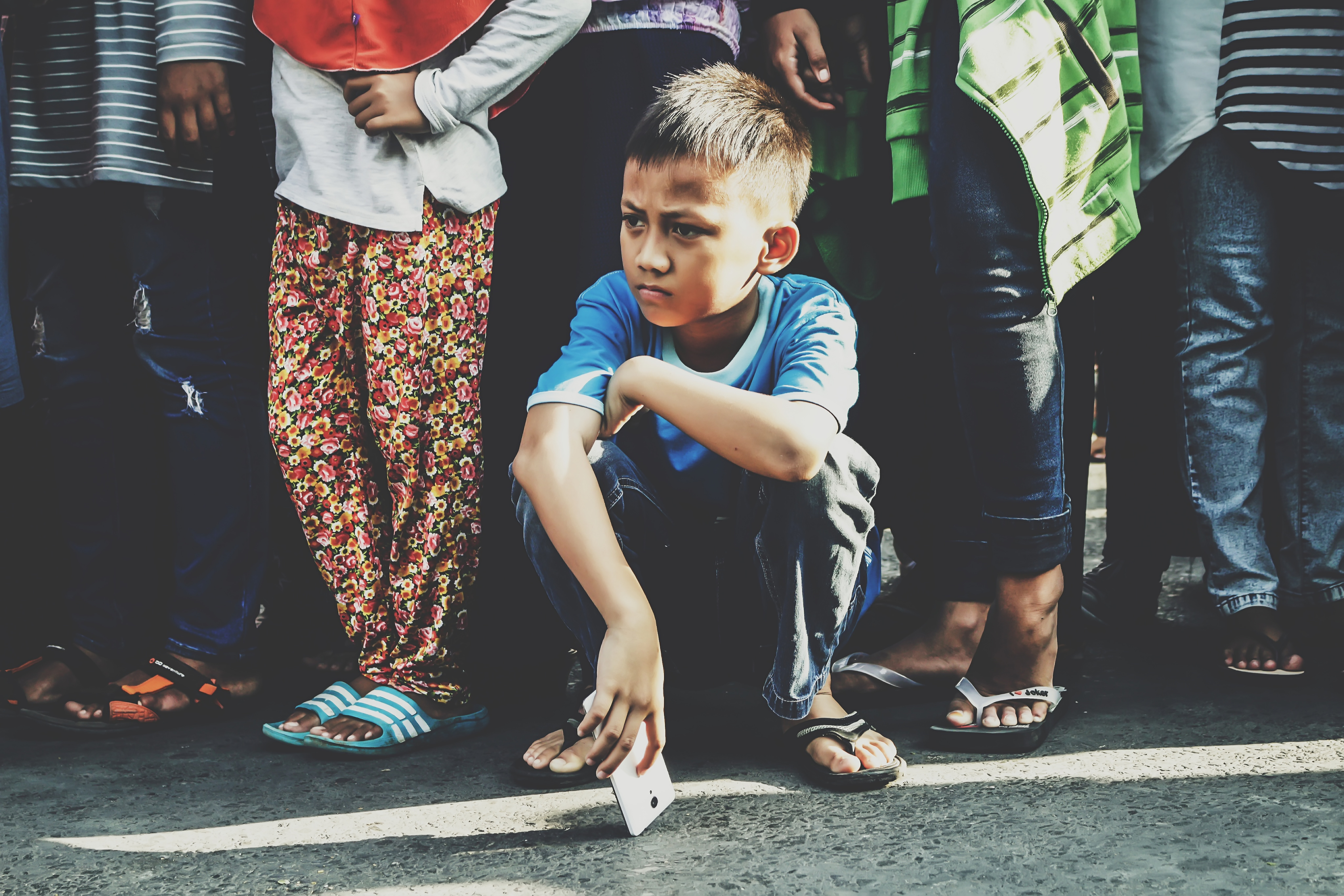 Upset looking boy squatting in front of a crowd