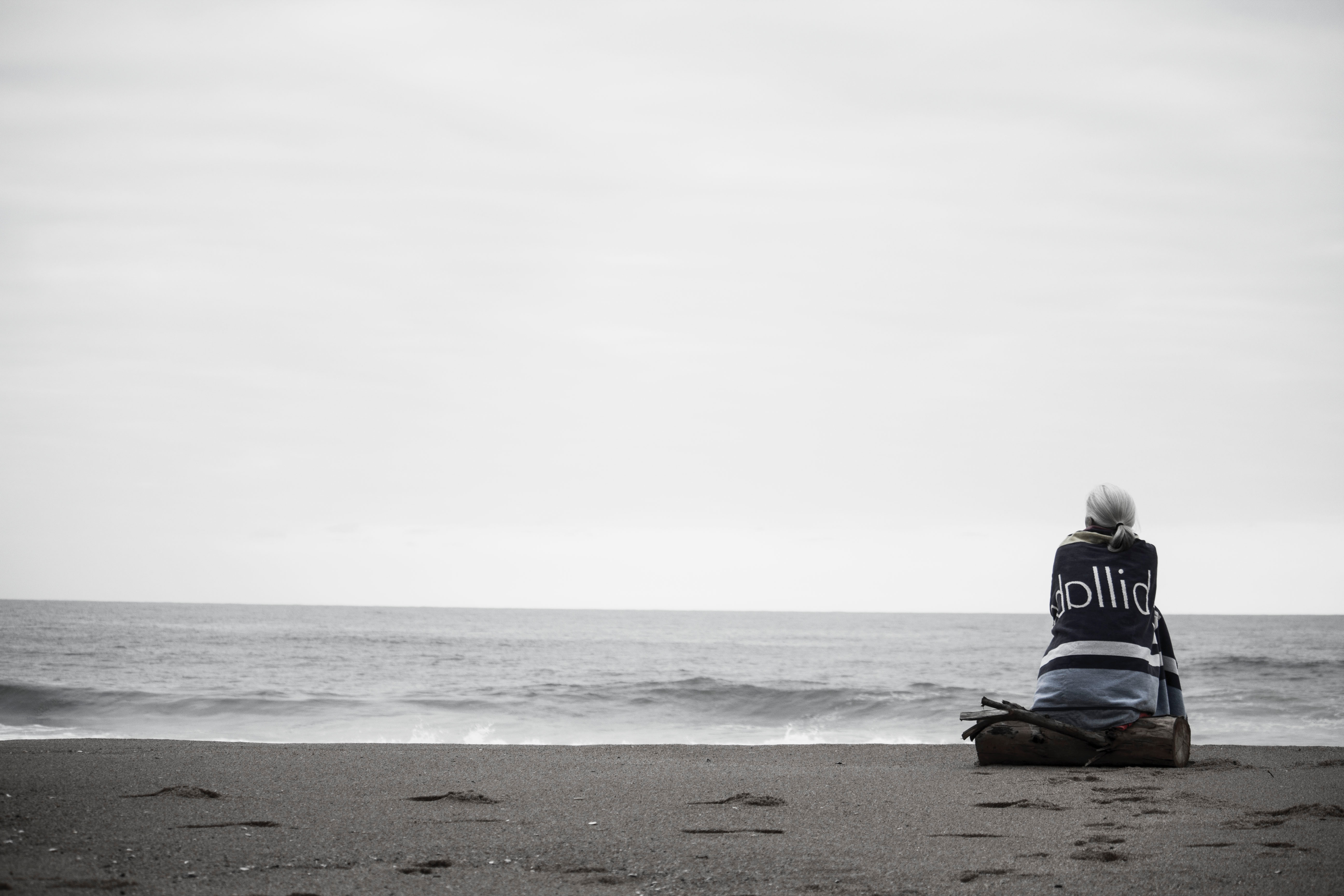 Woman sitting alone on the beach wrapped in a blanket