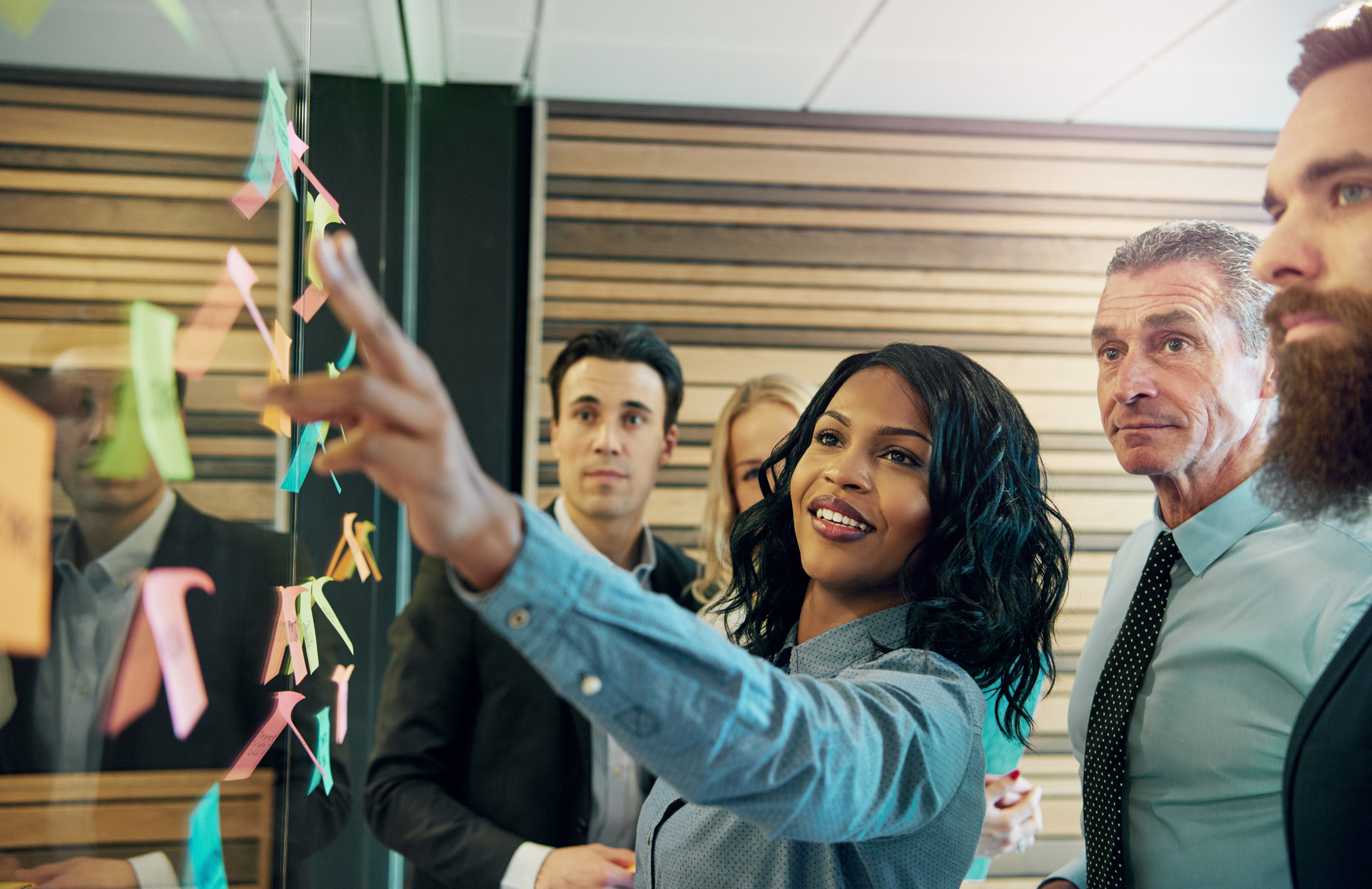 Young smiling black businesswoman at the wall with stickers communicating with her colleagues. Mixed team of entrepreneurs