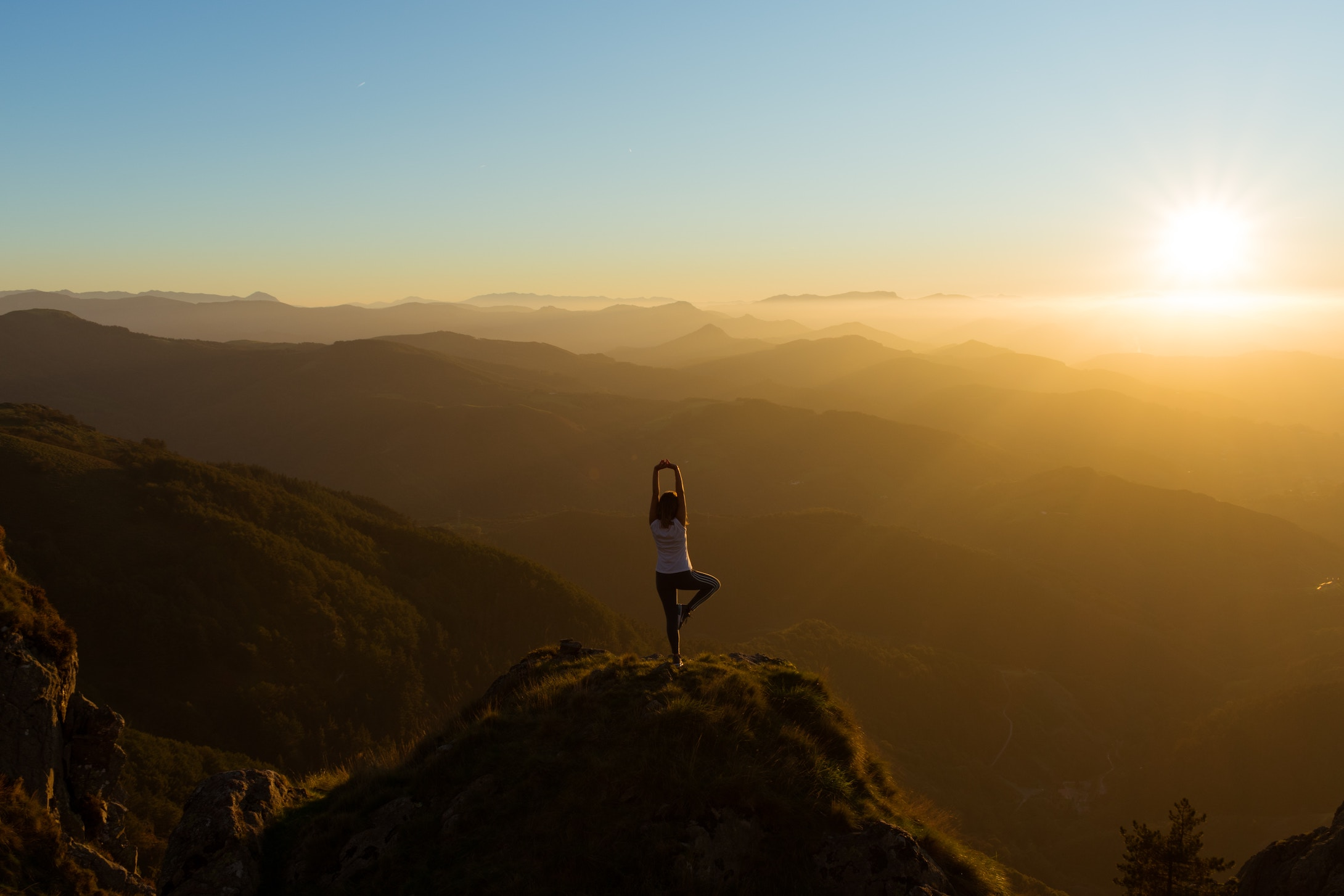 woman stretching on mountain top watching the sunrise