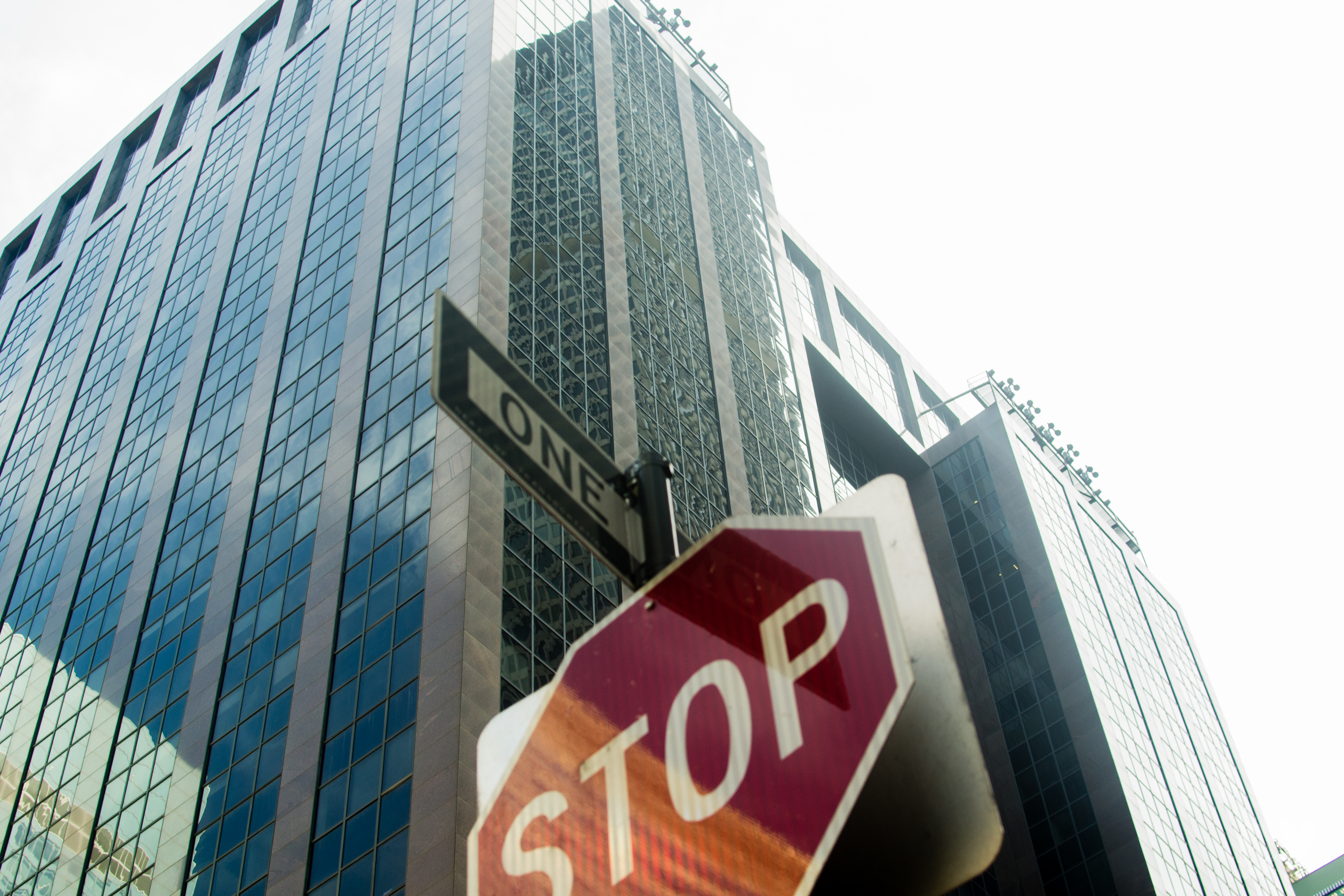 Perspective of a person looking up at a stop sign with skyscrapers in the background