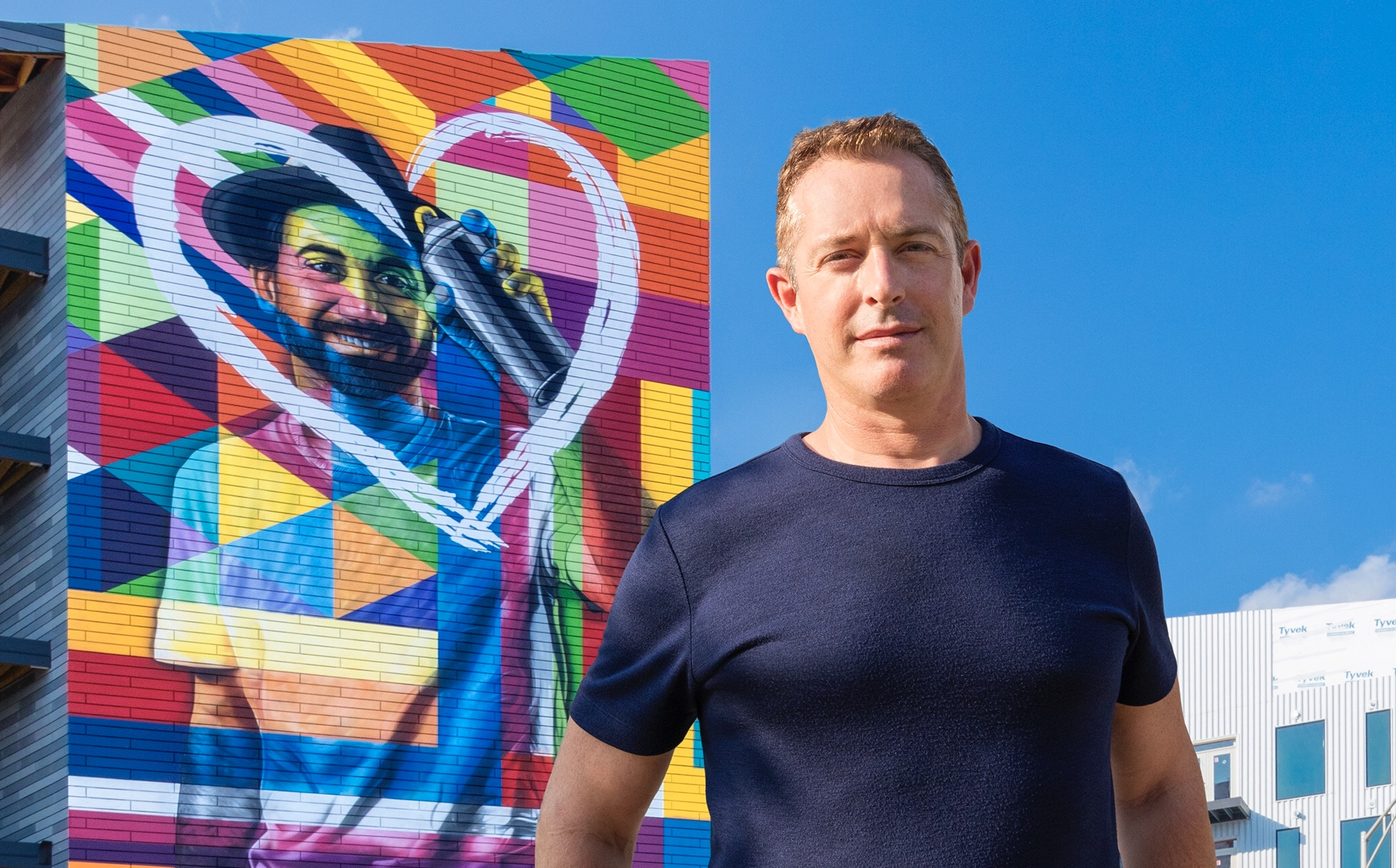 Brett in front of artist Eduardo Kobra's self-portrait mural at Gravity.