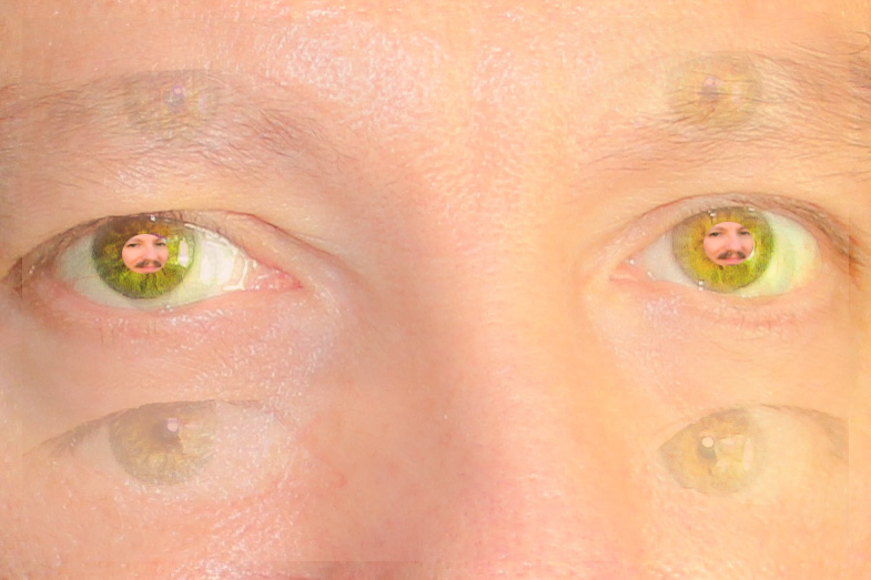 My eyes reflected in a mirror , my face reflected in my eyes.