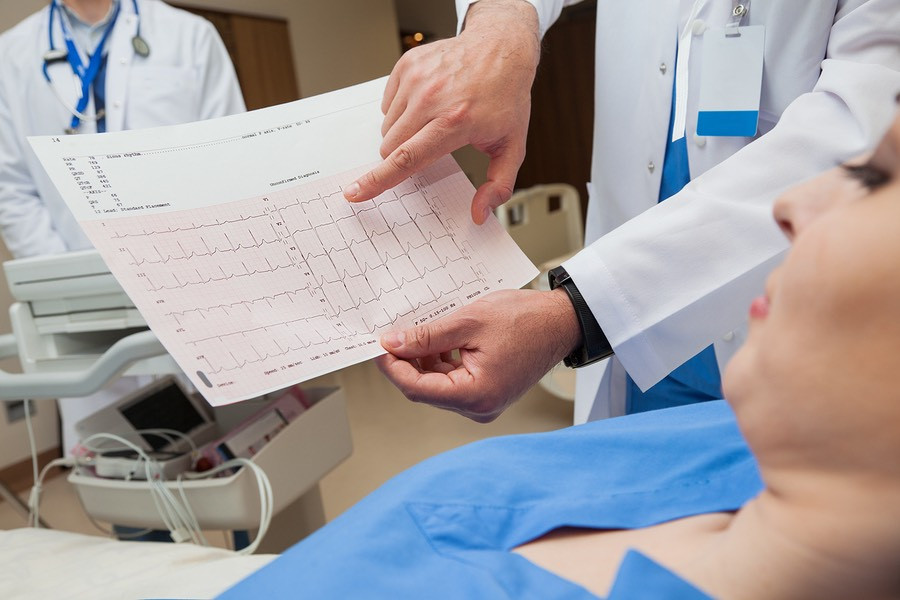 Close-up of a doctor, hands only, showing a normal sinus rhythm sheet to a young female patient.