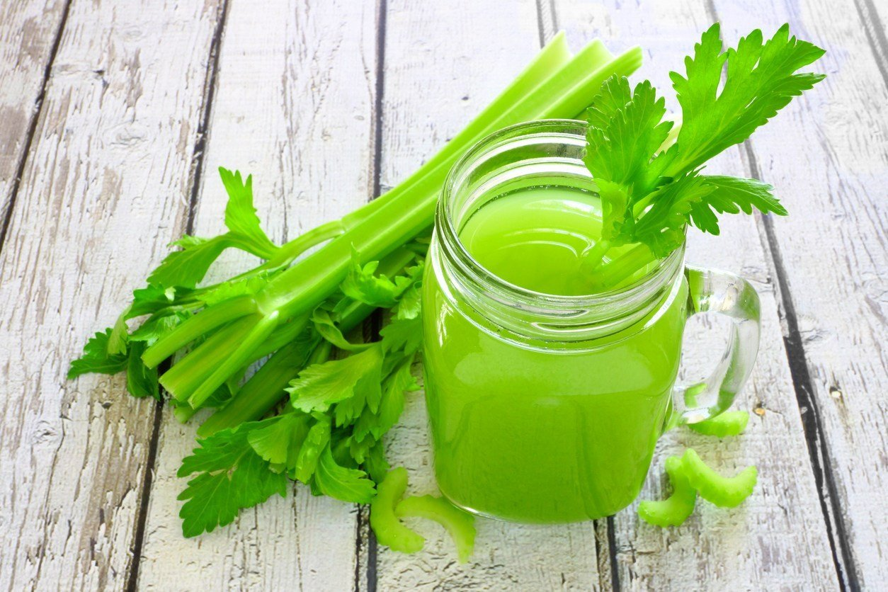 Celery juice in a mason jar glass. Downward view over a rustic white wood background.