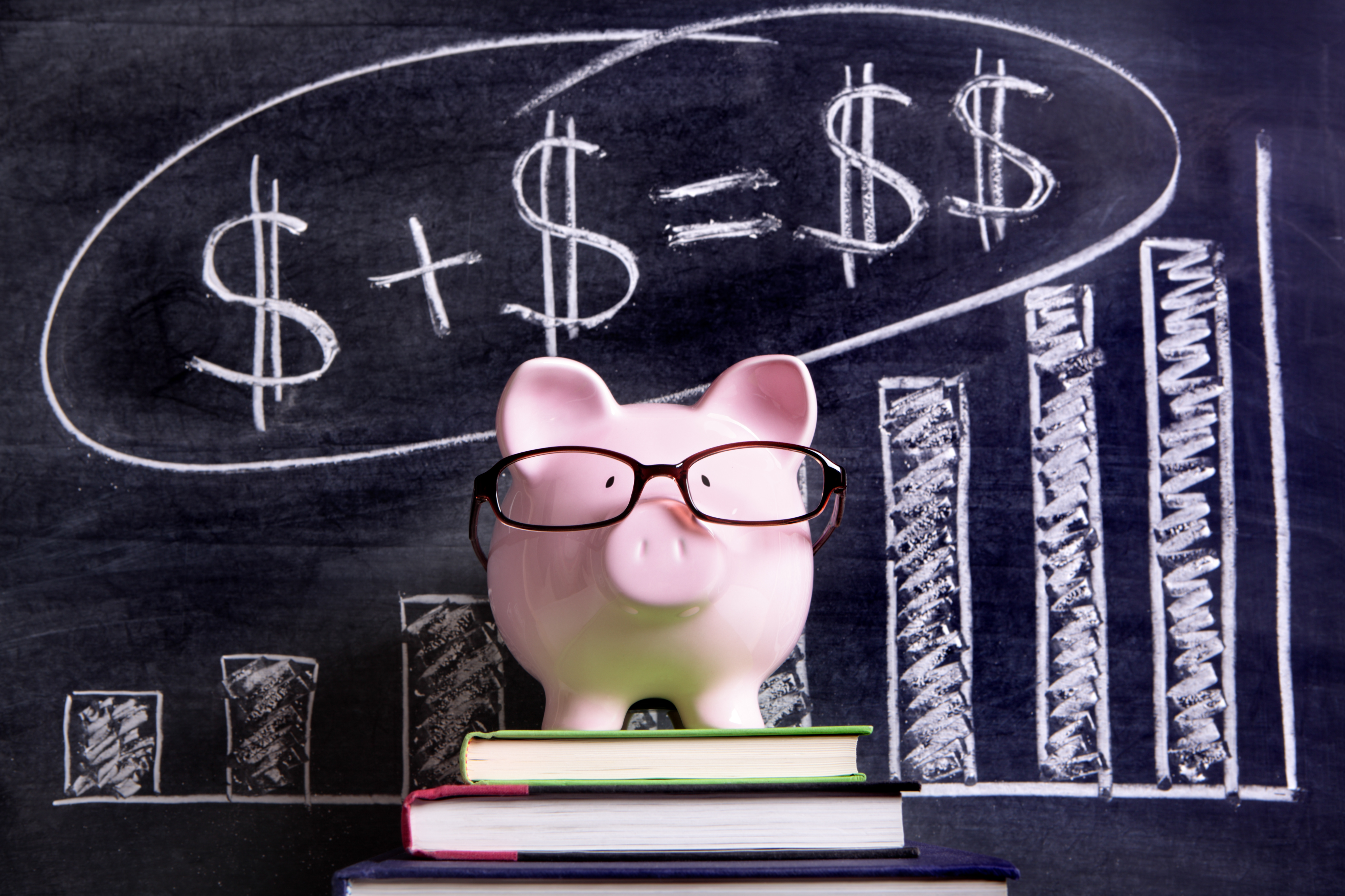 Pink piggy bank with glasses standing on books next to a blackboard with simple money math.  Sharp focus on the piggy bank with blackboard slightly blurred.