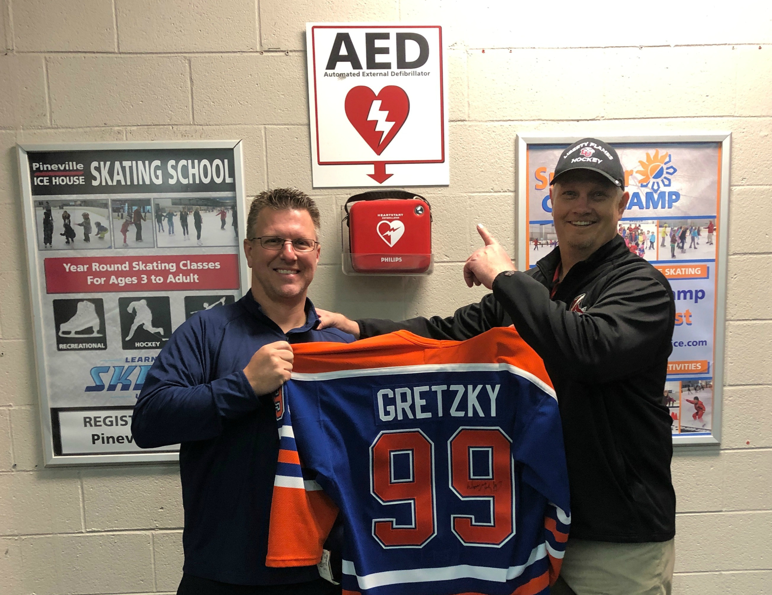 Jib Street (right) and Dr. Craig Bryant at the Pineville Ice House. The signed Wayne Gretzky jersey was Jib's thank-you gift to Craig for using the AED to save his life. (Photo courtesy of Jib Street)