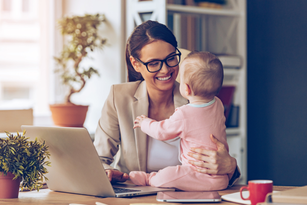 A working mom interacts with her baby on her desk