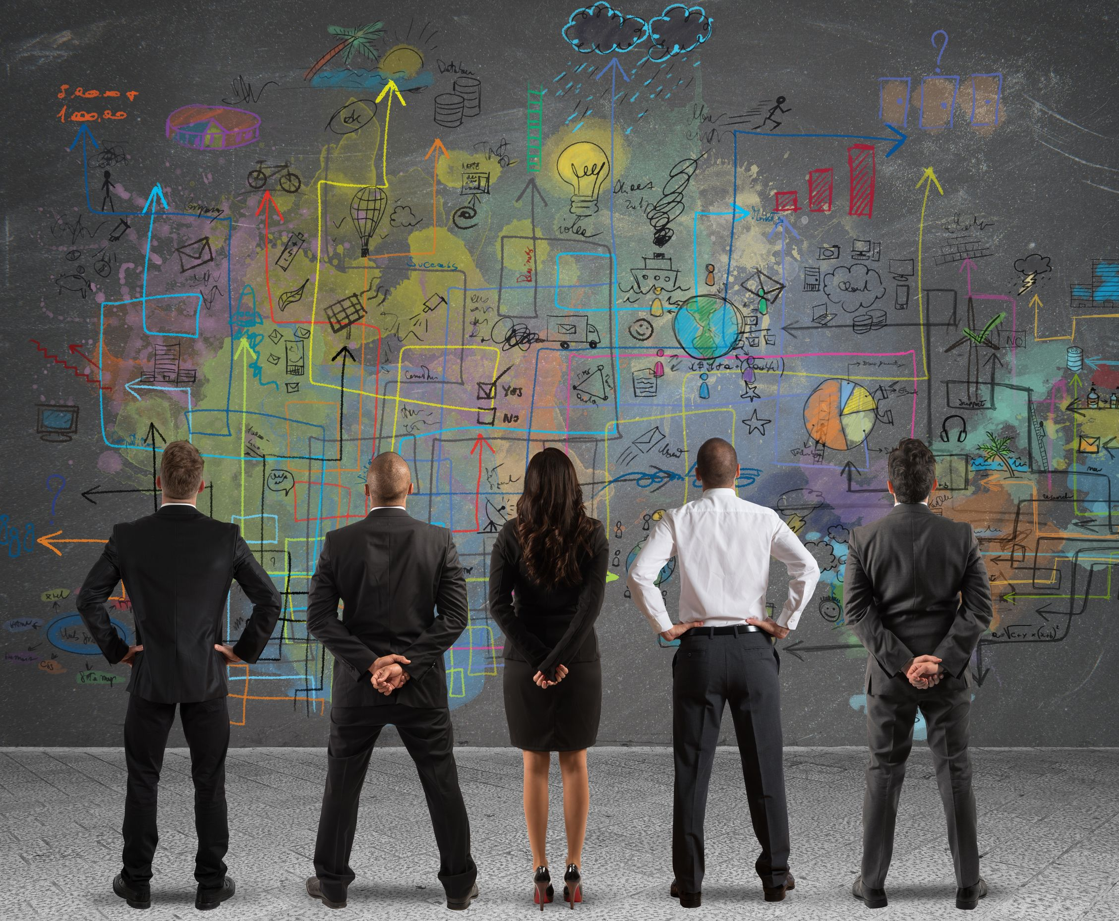 A business team looks at a large strategy painted on the wall.