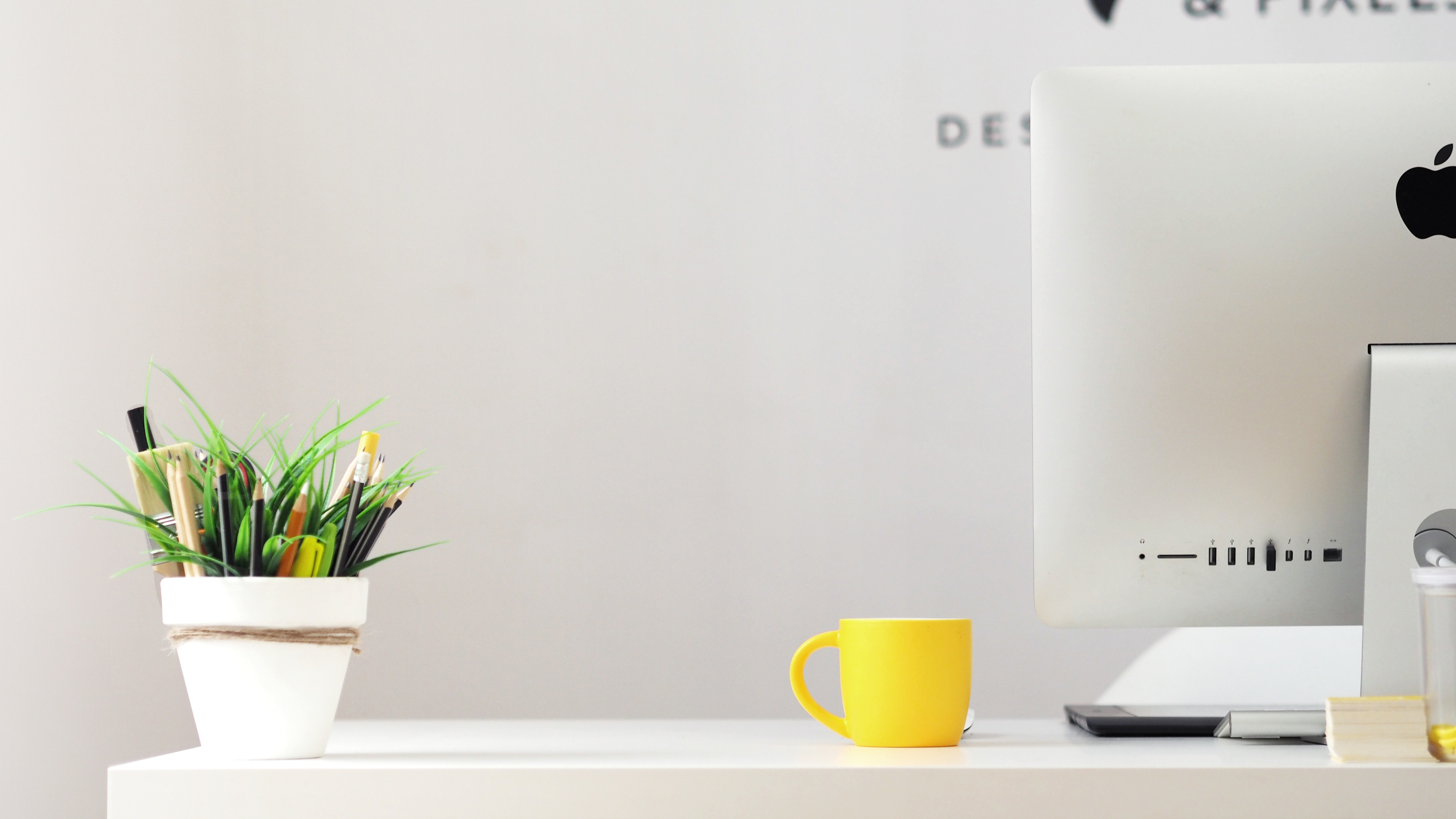 a home office desk with yellow mug and houseplant