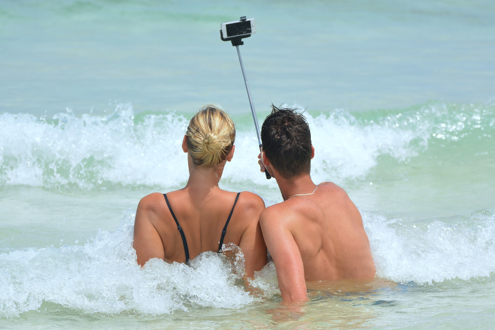 two young people, female and male, taking selfie on the beach